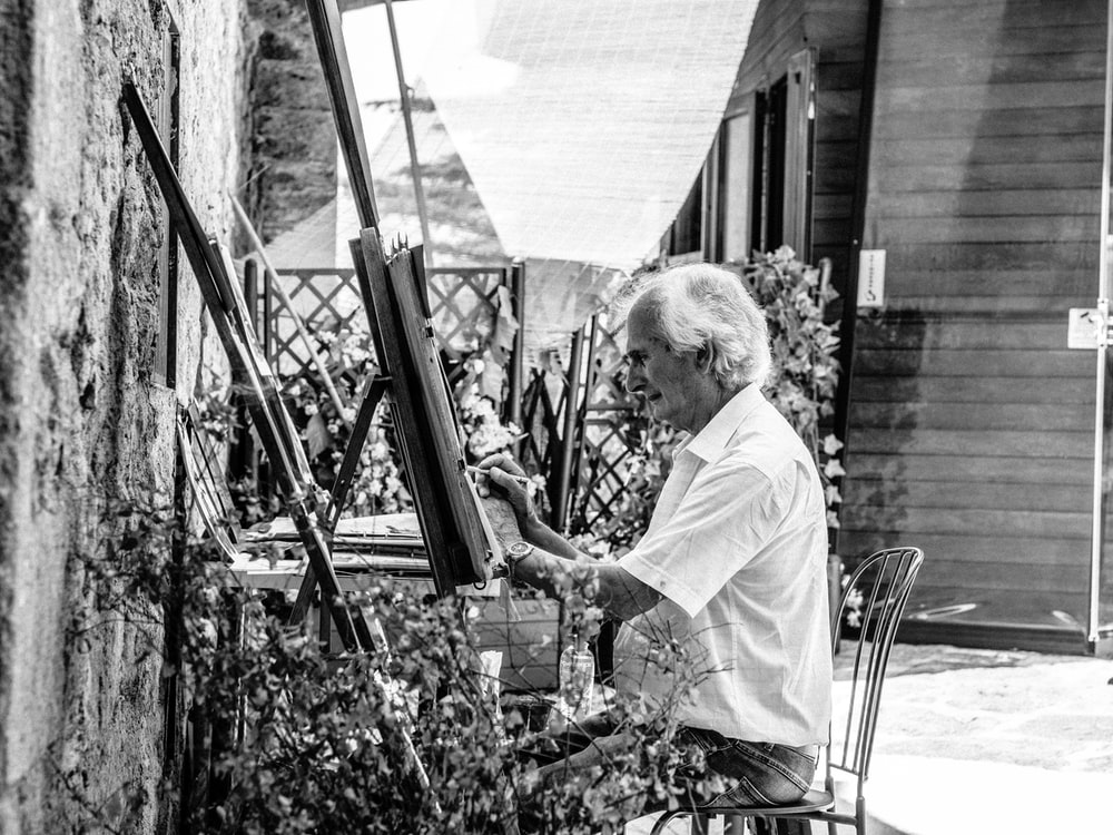 grayscale photo of man sitting while painting