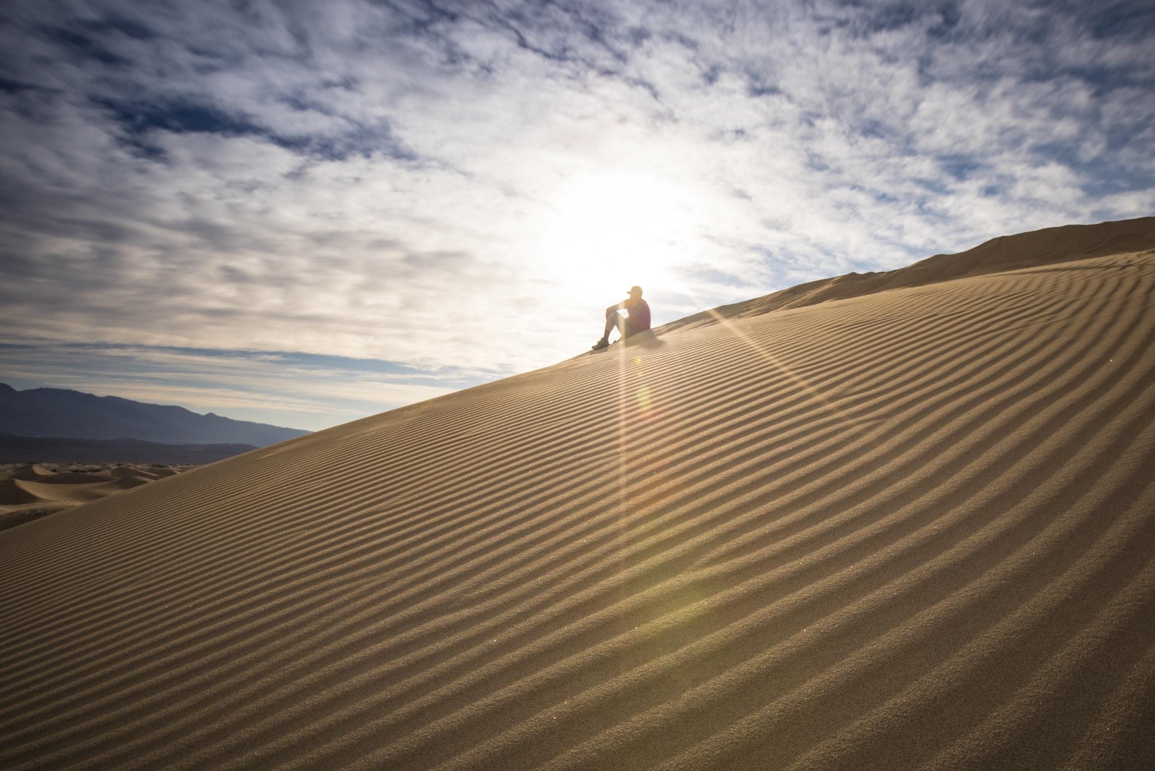 person sitting on desert during daytime