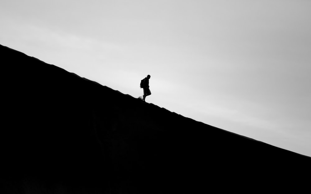 silhouette photo of person walking on mountain
