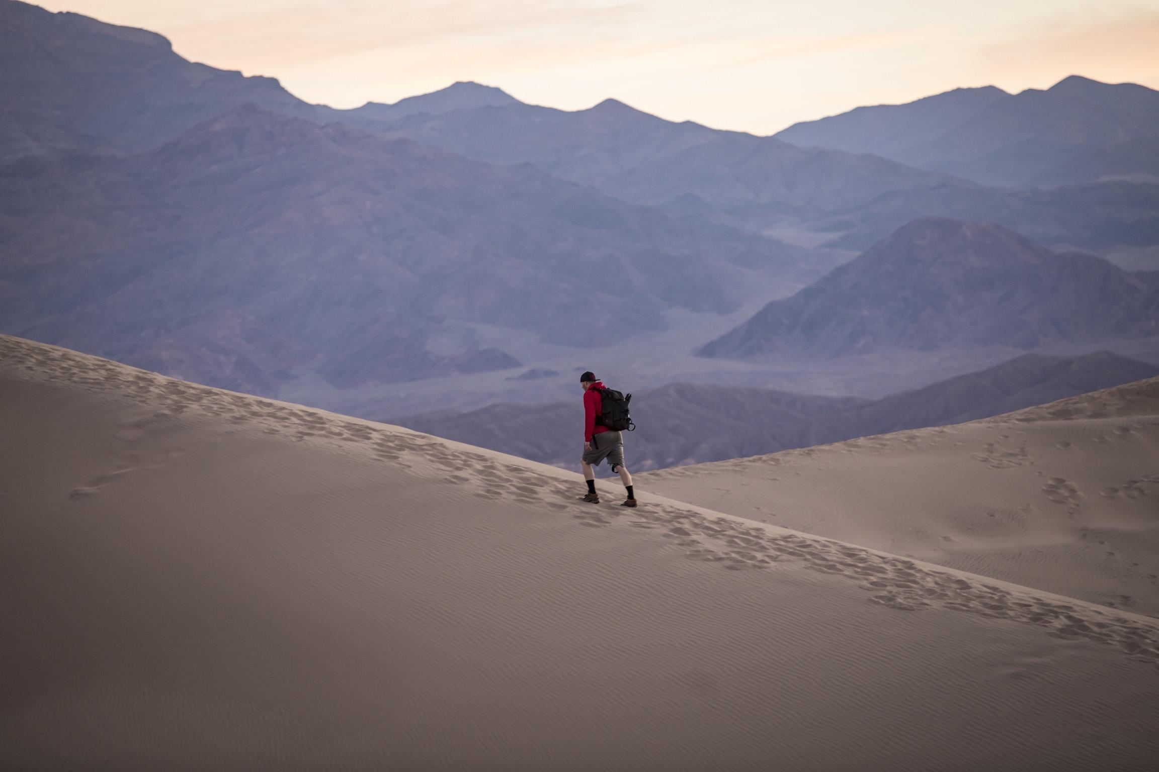 person in red hoodie walking on desert