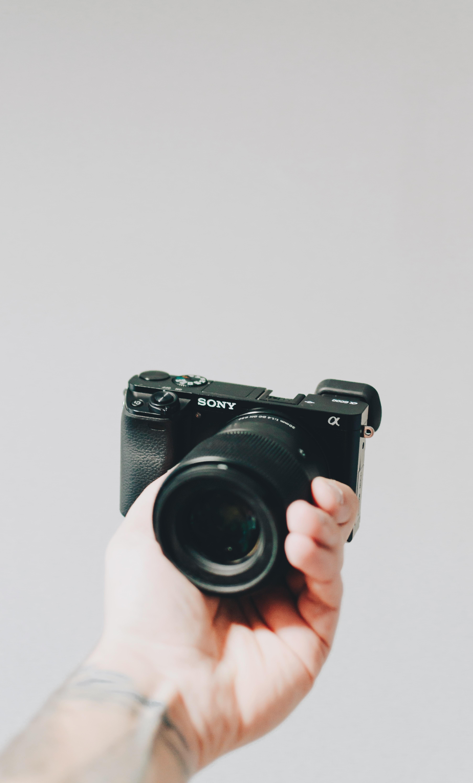 person holding black Sony Alpha camera