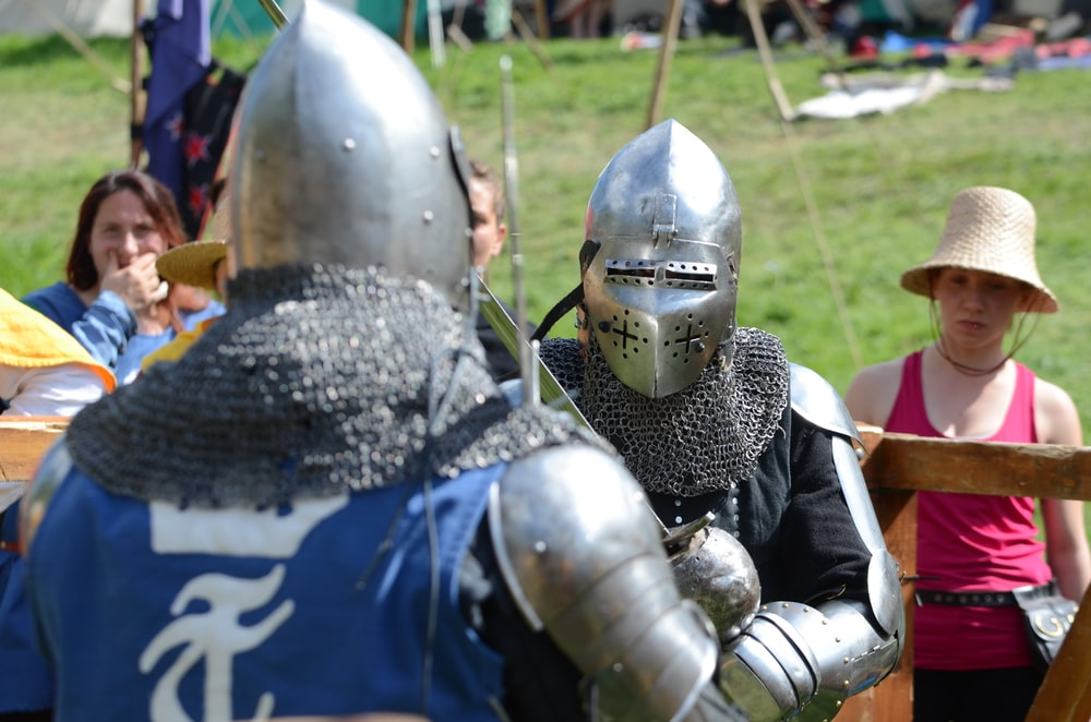 two men wearing silver armor facing each other