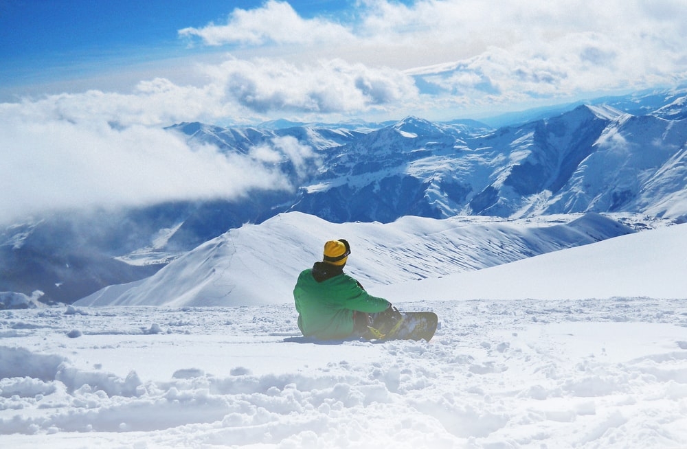 man snowboarding on snow during daytime