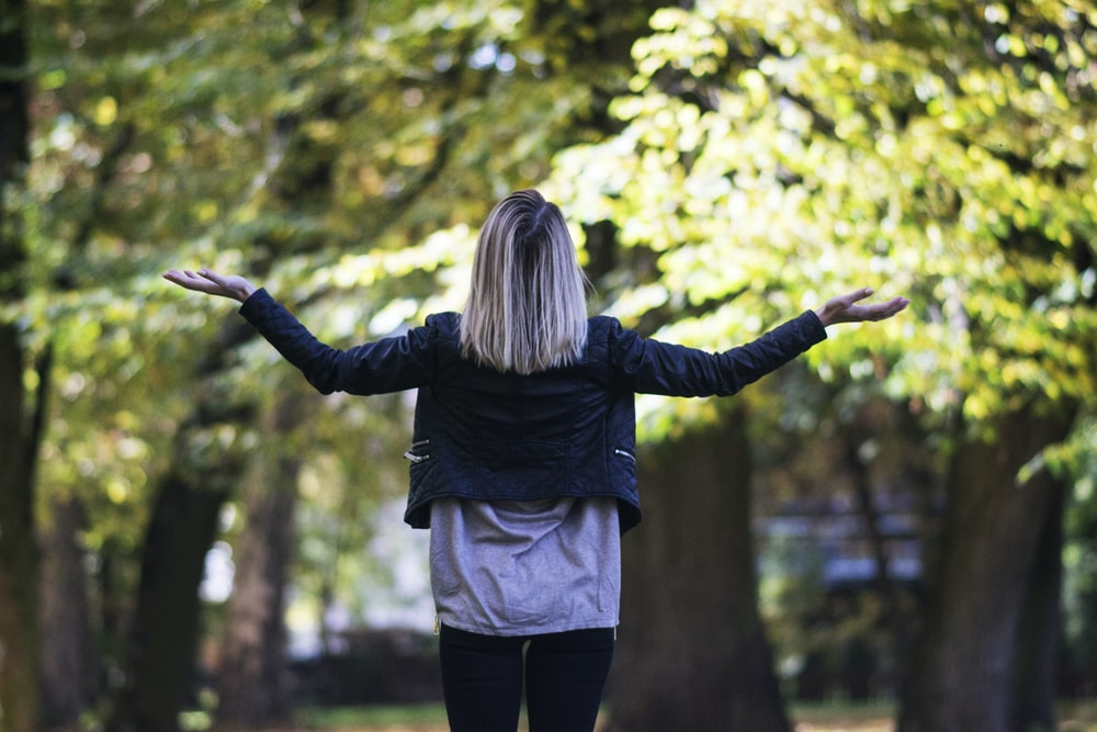 Visual of a woman in black long-sleeved top in front of green-leafed tree
