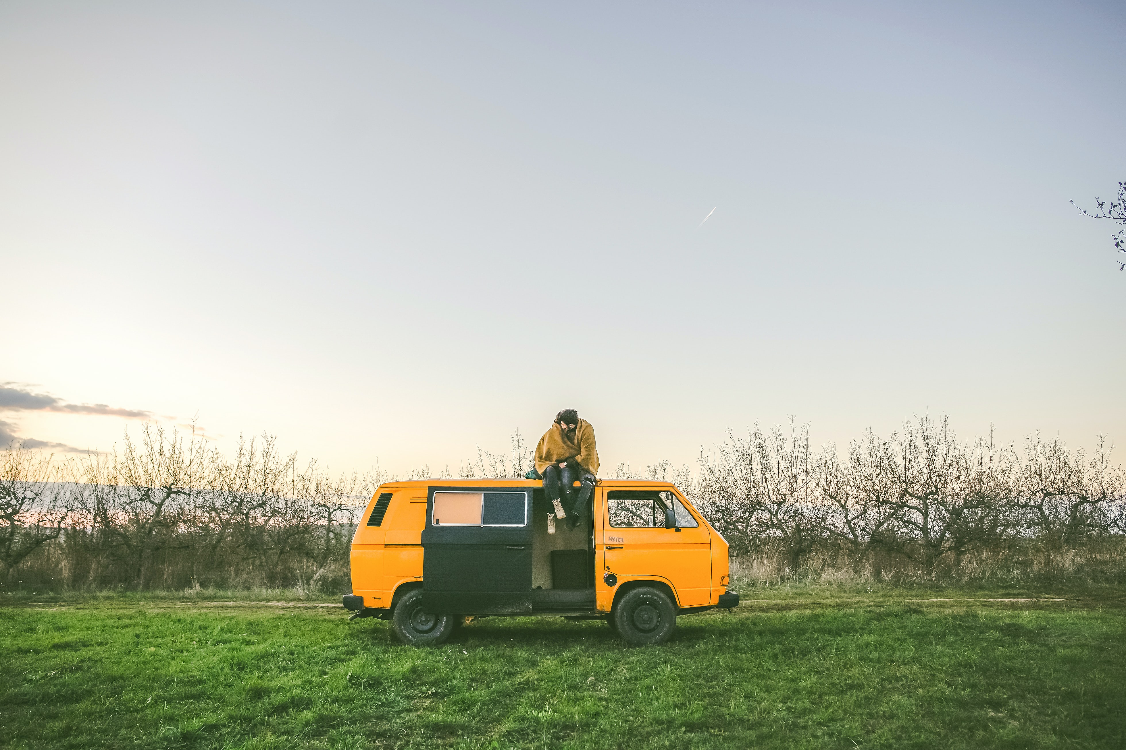 person sitting on top of yellow van on grass field during day