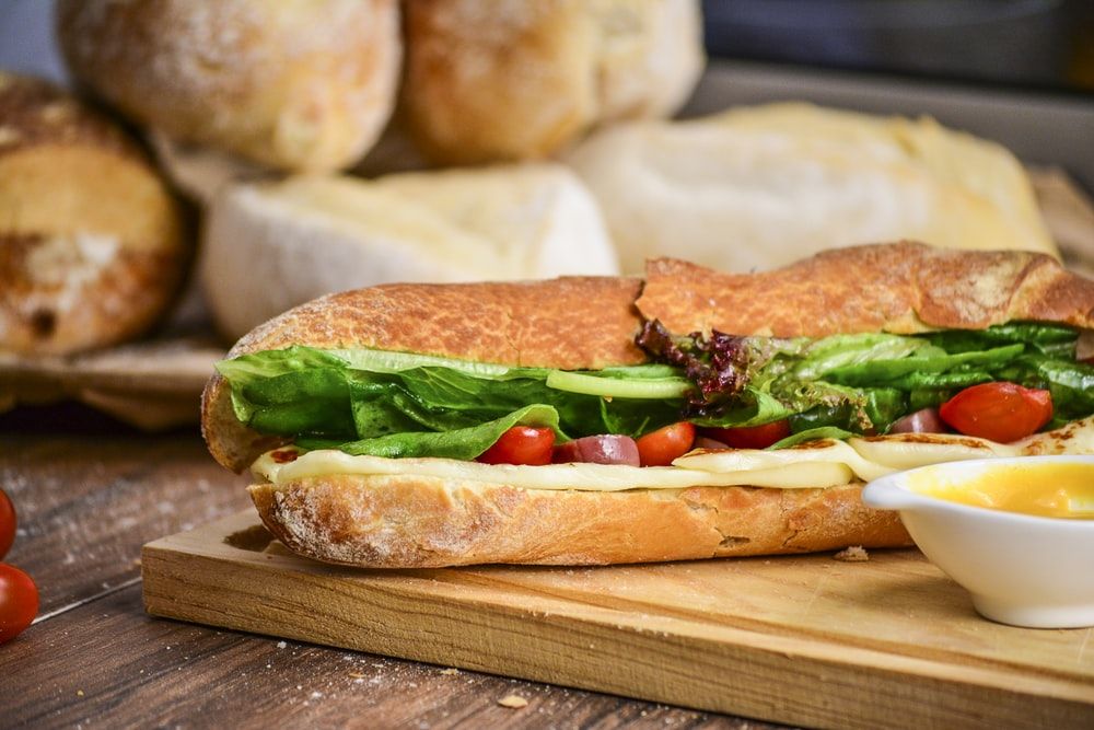 baked bread with vegetable on brown chopping board
