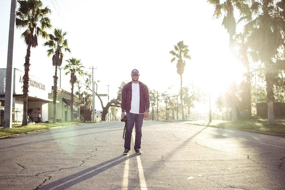 man holding black DSLR camera standing on road during daytime
