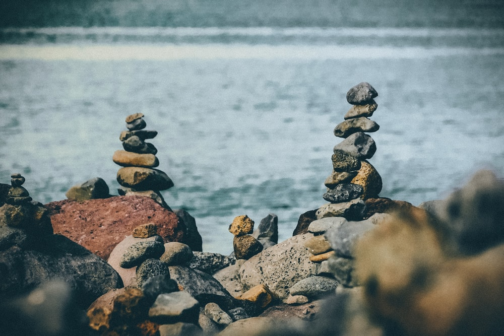 photo of balance rocks near body of water