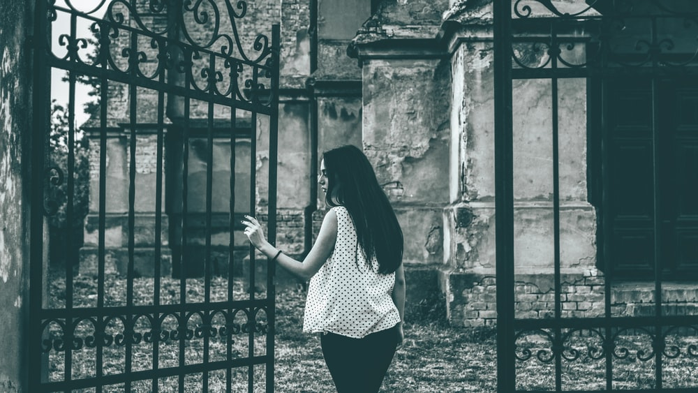 grayscale photo of standing woman beside metal gate