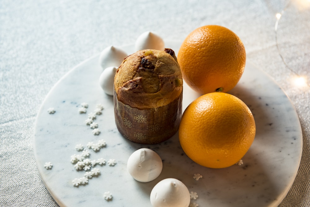 two orange fruits on white plate