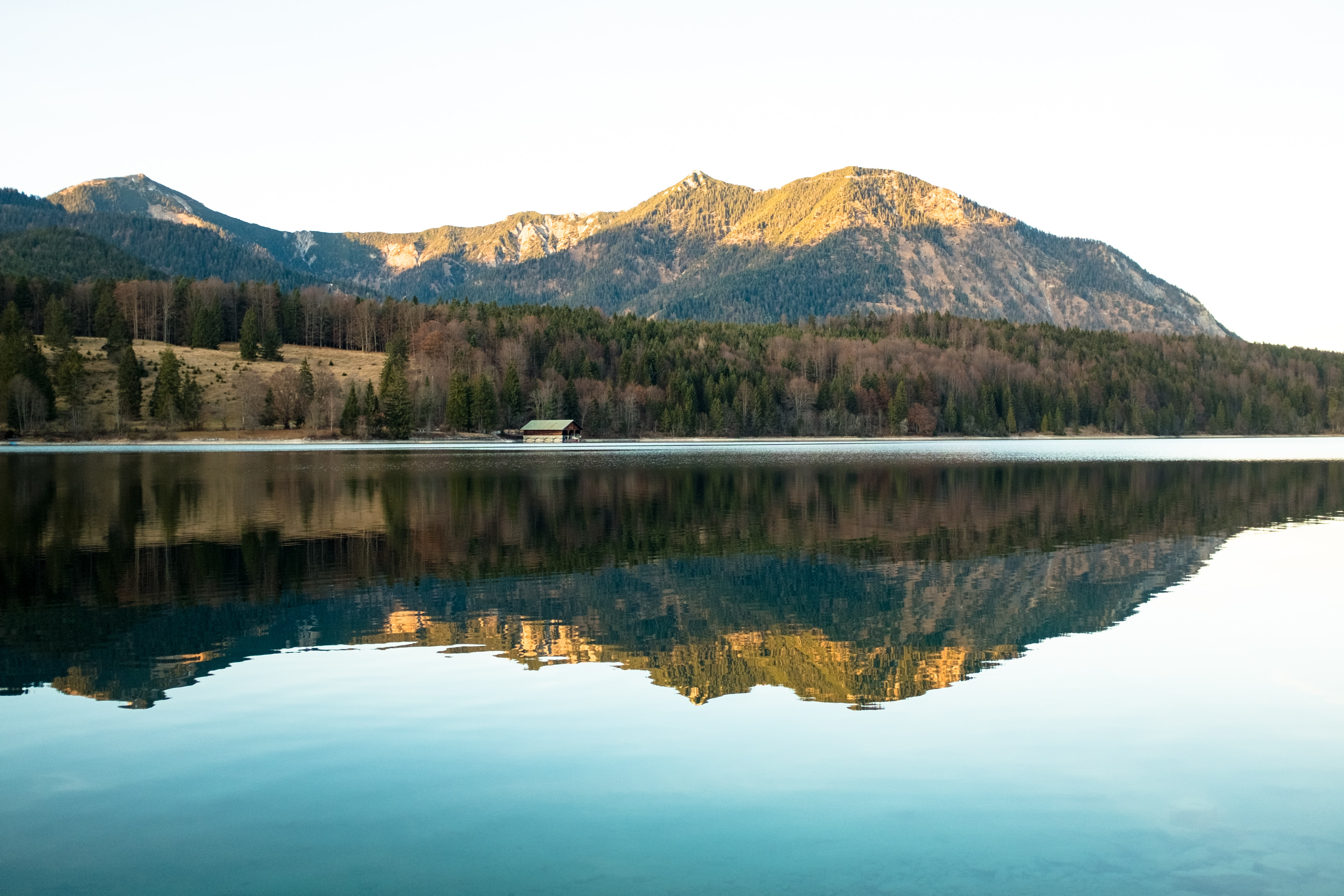 body of water reflecting green mountain at daytime