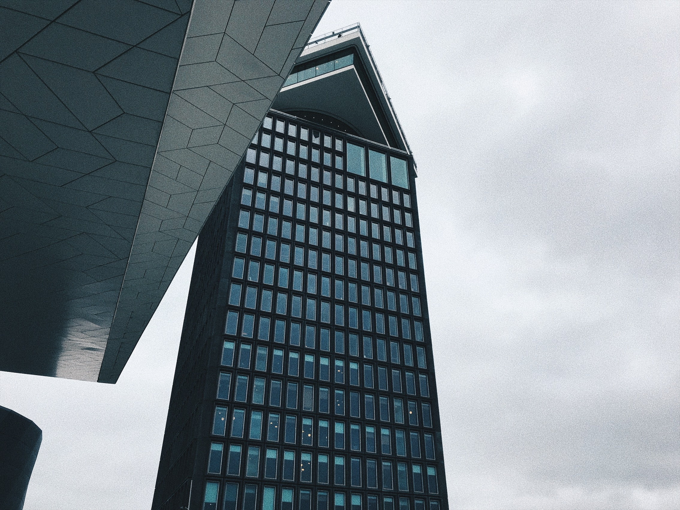 photo of black concrete building with glass under cloudy sky
