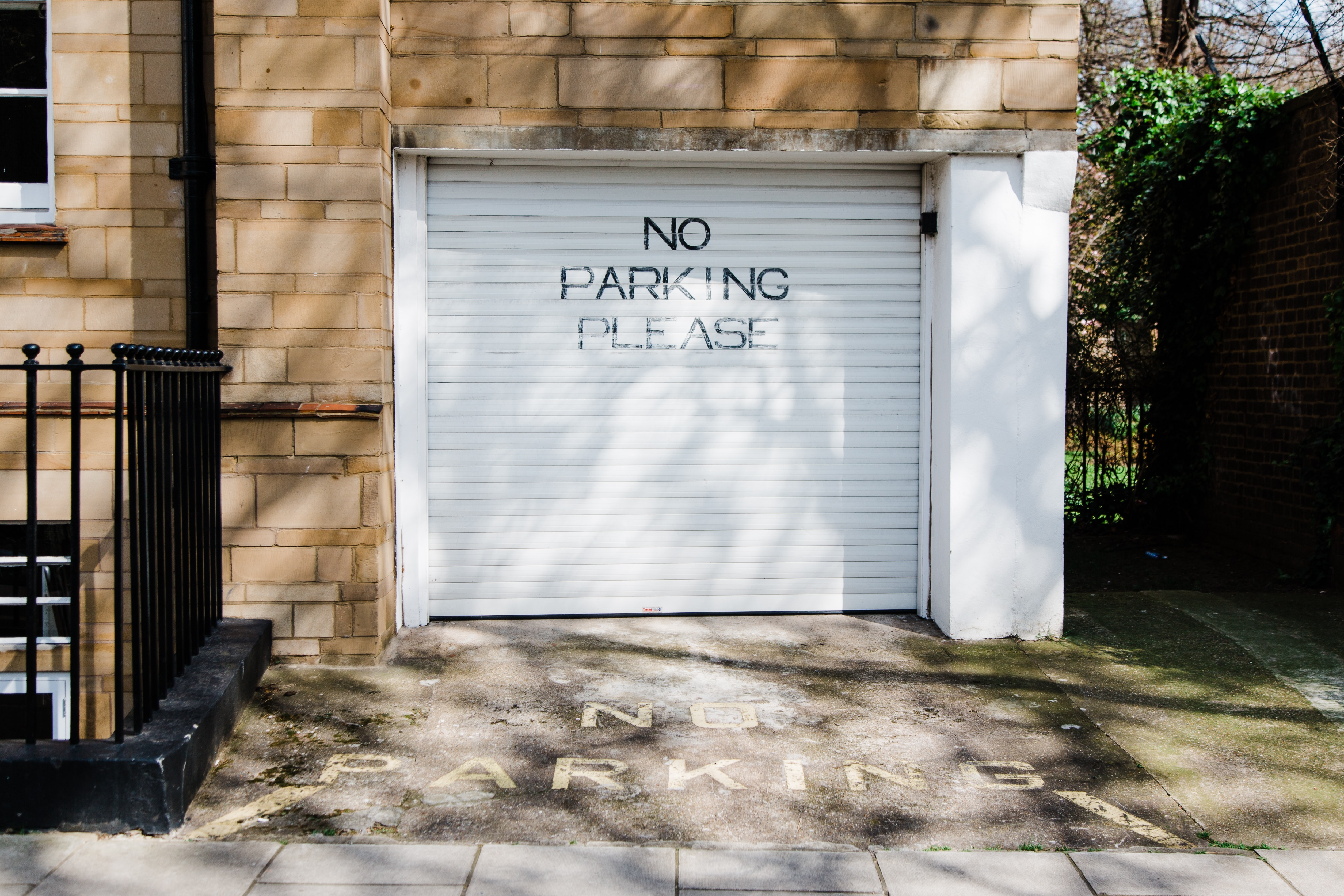 gray metal roll-up door with no parking please printed
