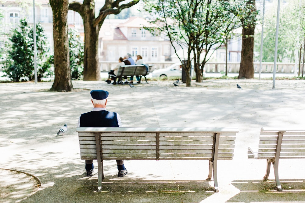 person sitting on beige street bench near trees