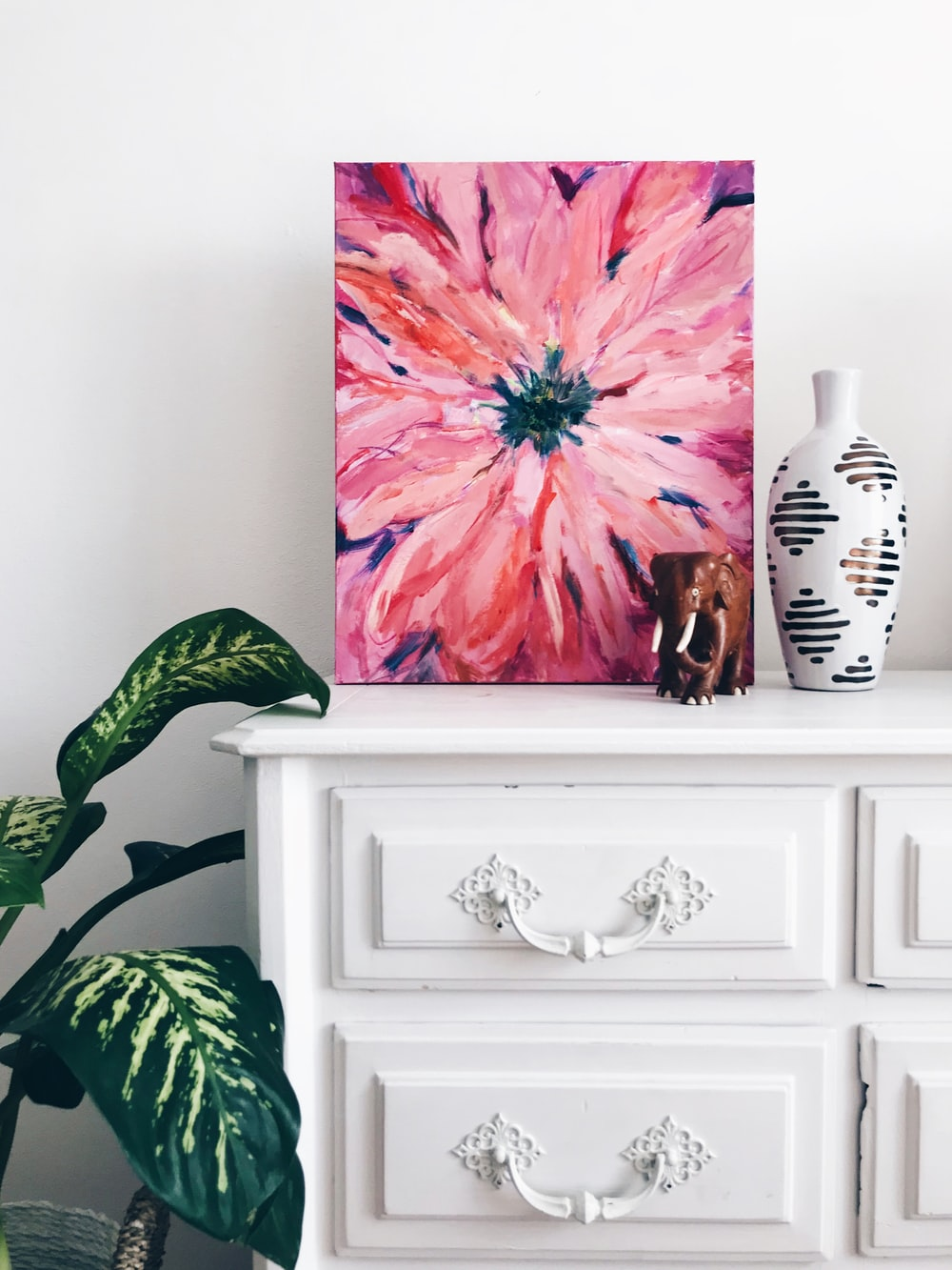 painting of pink flower on dresser near white vase