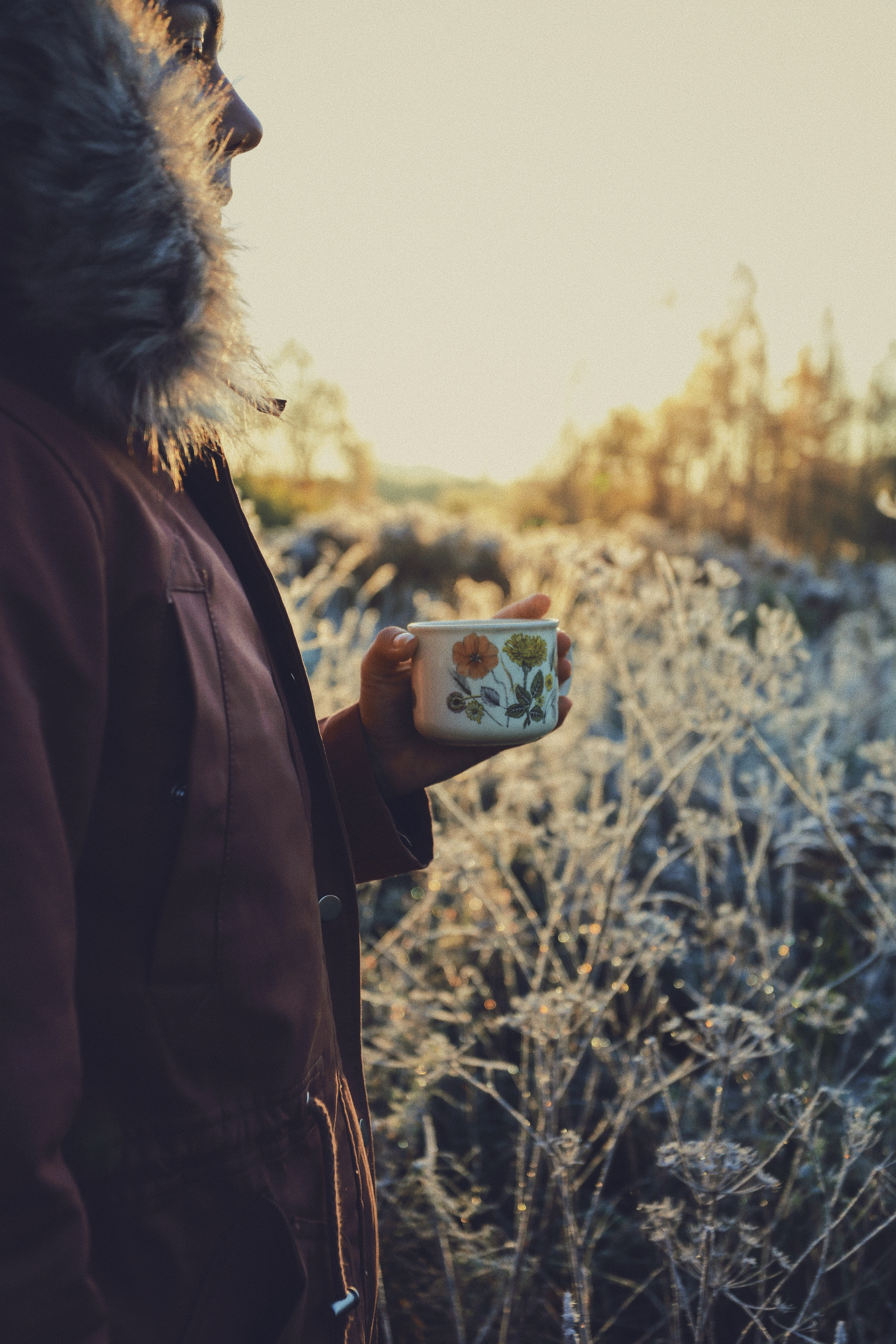 person in red fur-lined jacket holding white and green floral mug