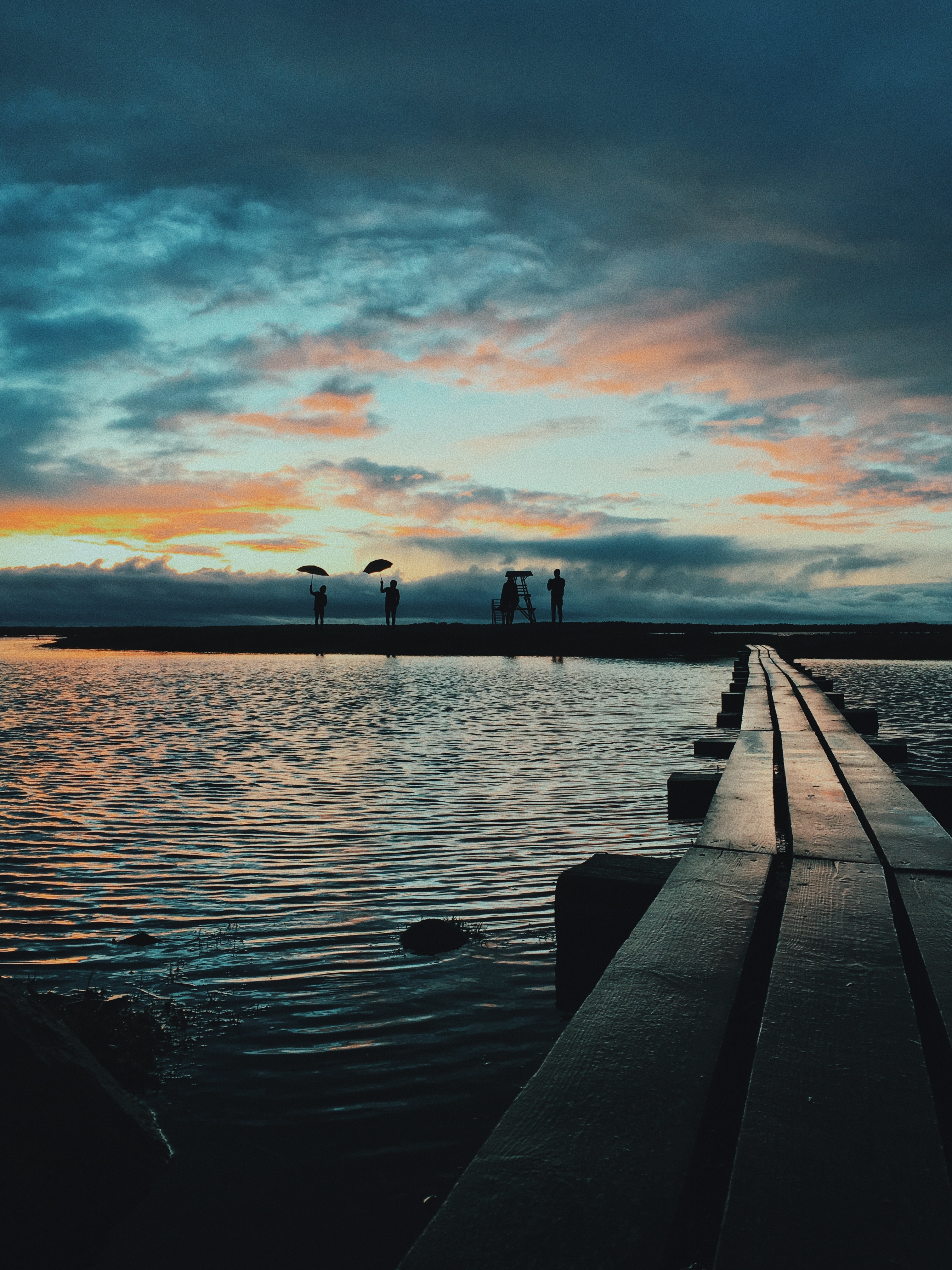 silhouette of four persons on dock