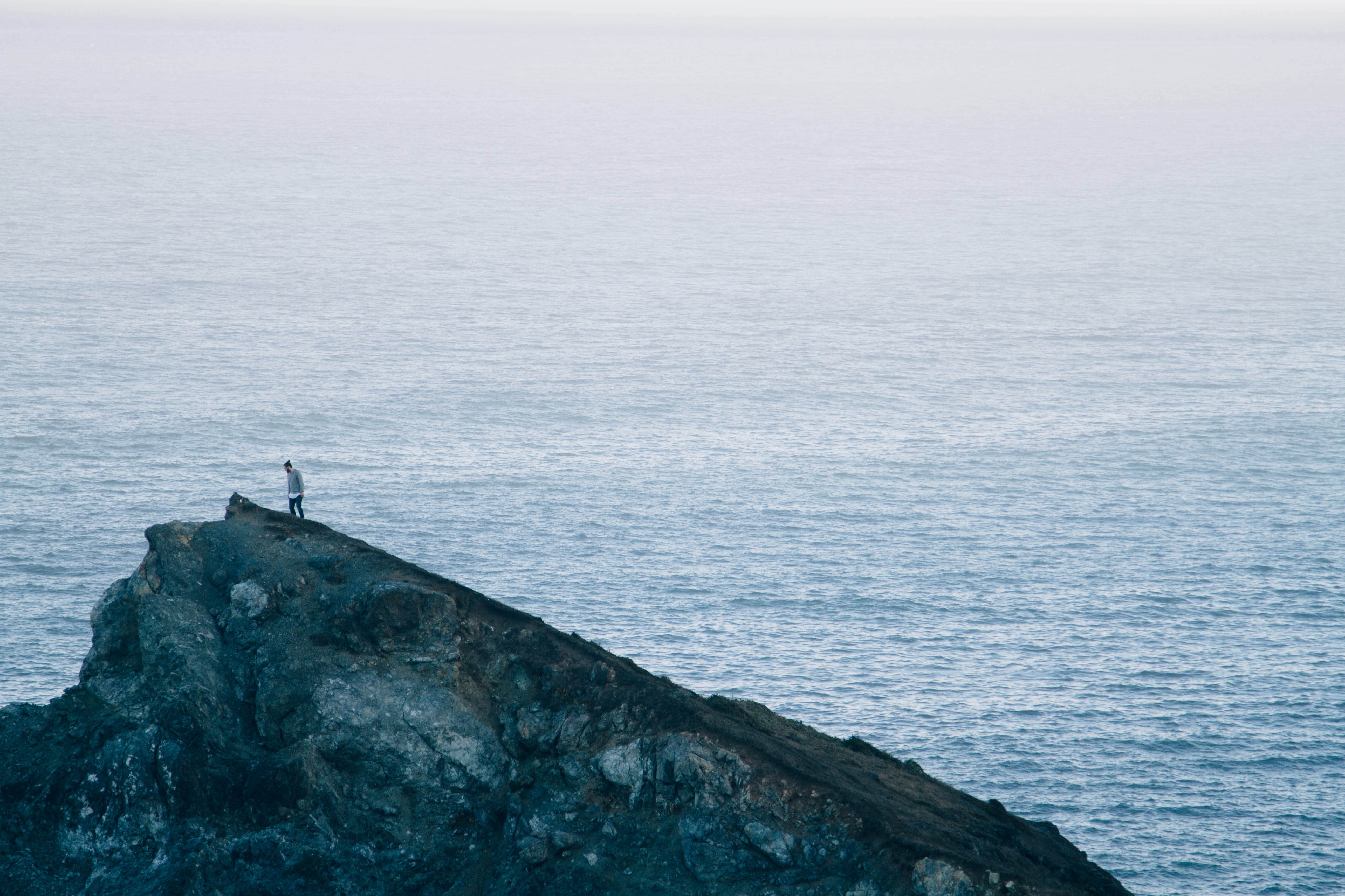 person standing on gray rock formation near body of water during daytime