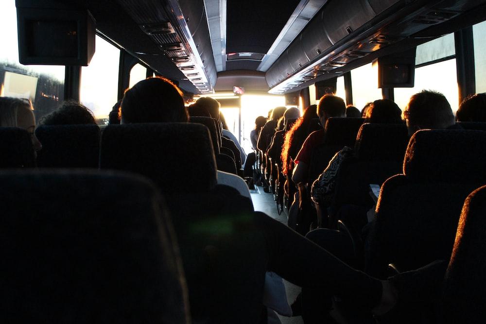 people riding passenger bus during daytime