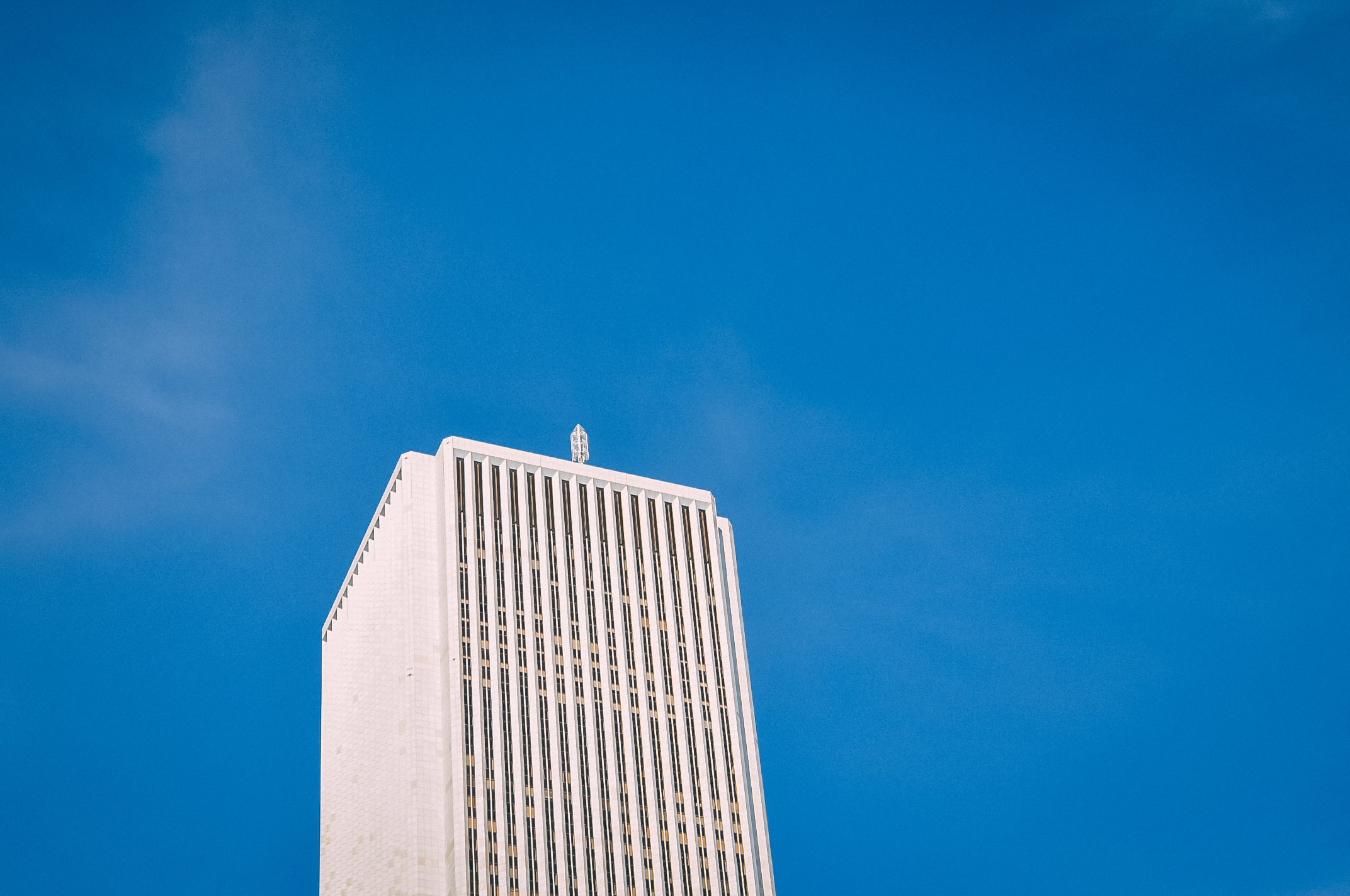 low angle photo of white high-rise building under blue sky