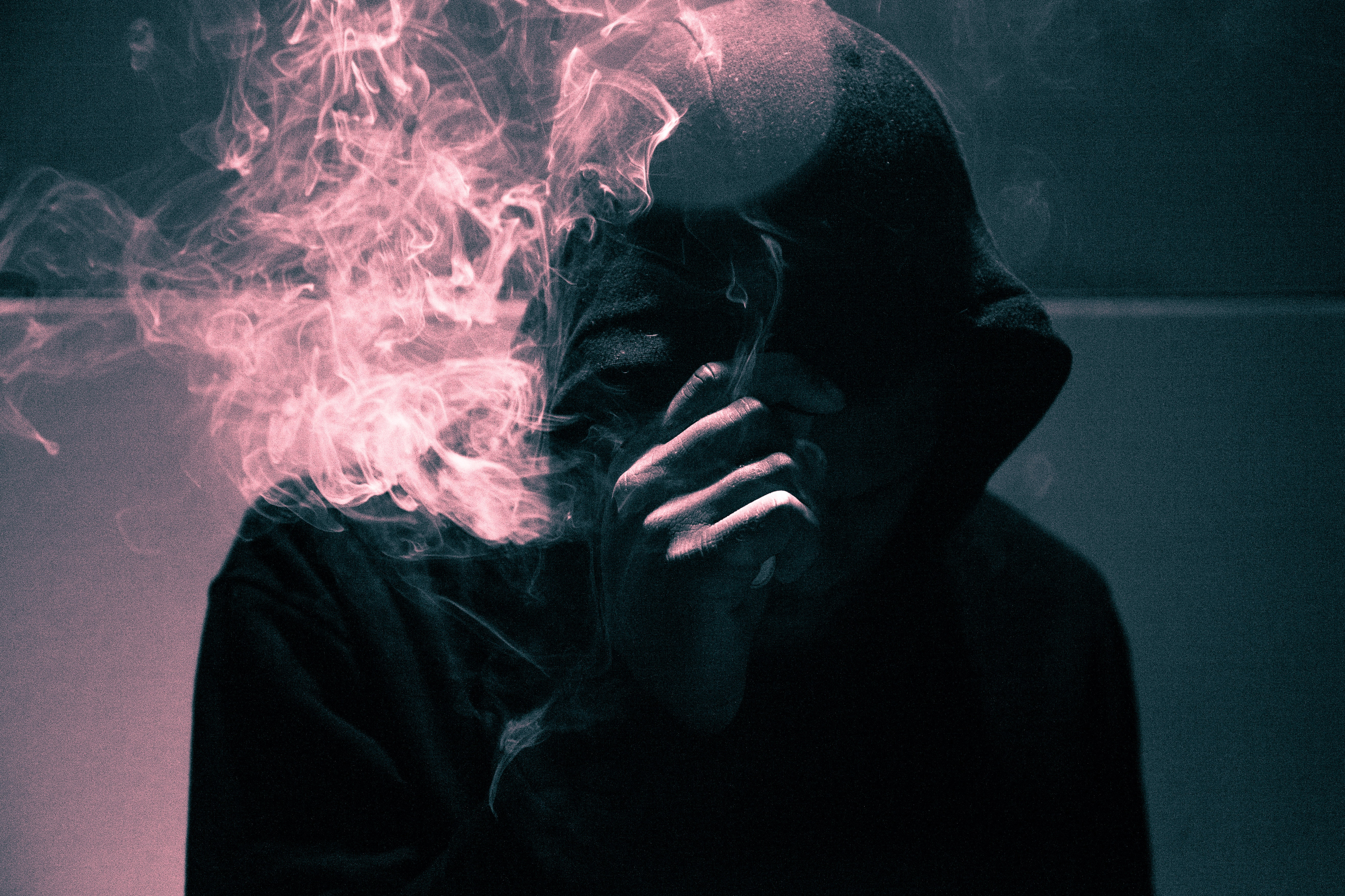 man standing near the wall while smoking