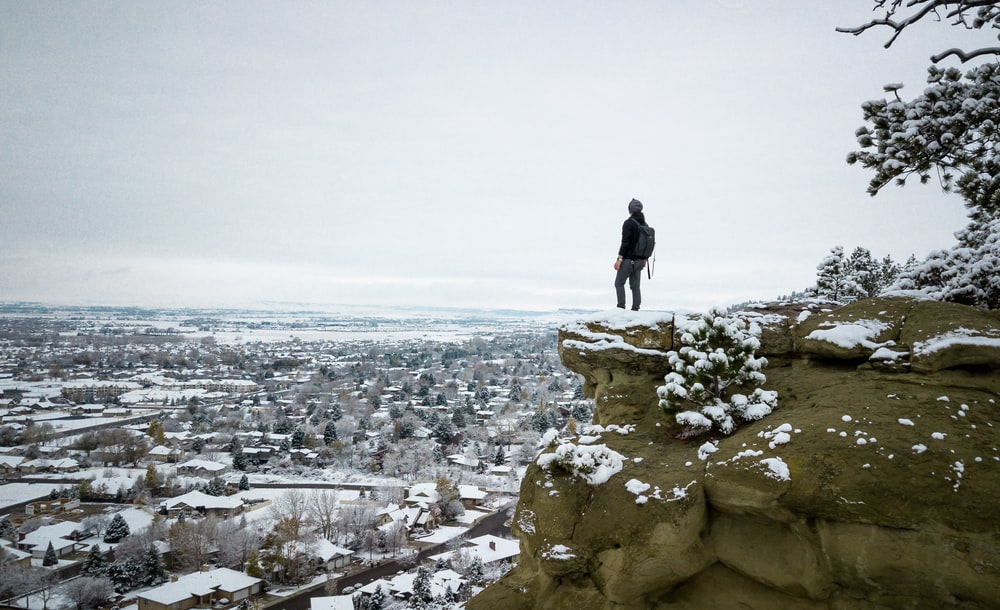 person standing on cliff of gray rocky mountain with snow during daytime