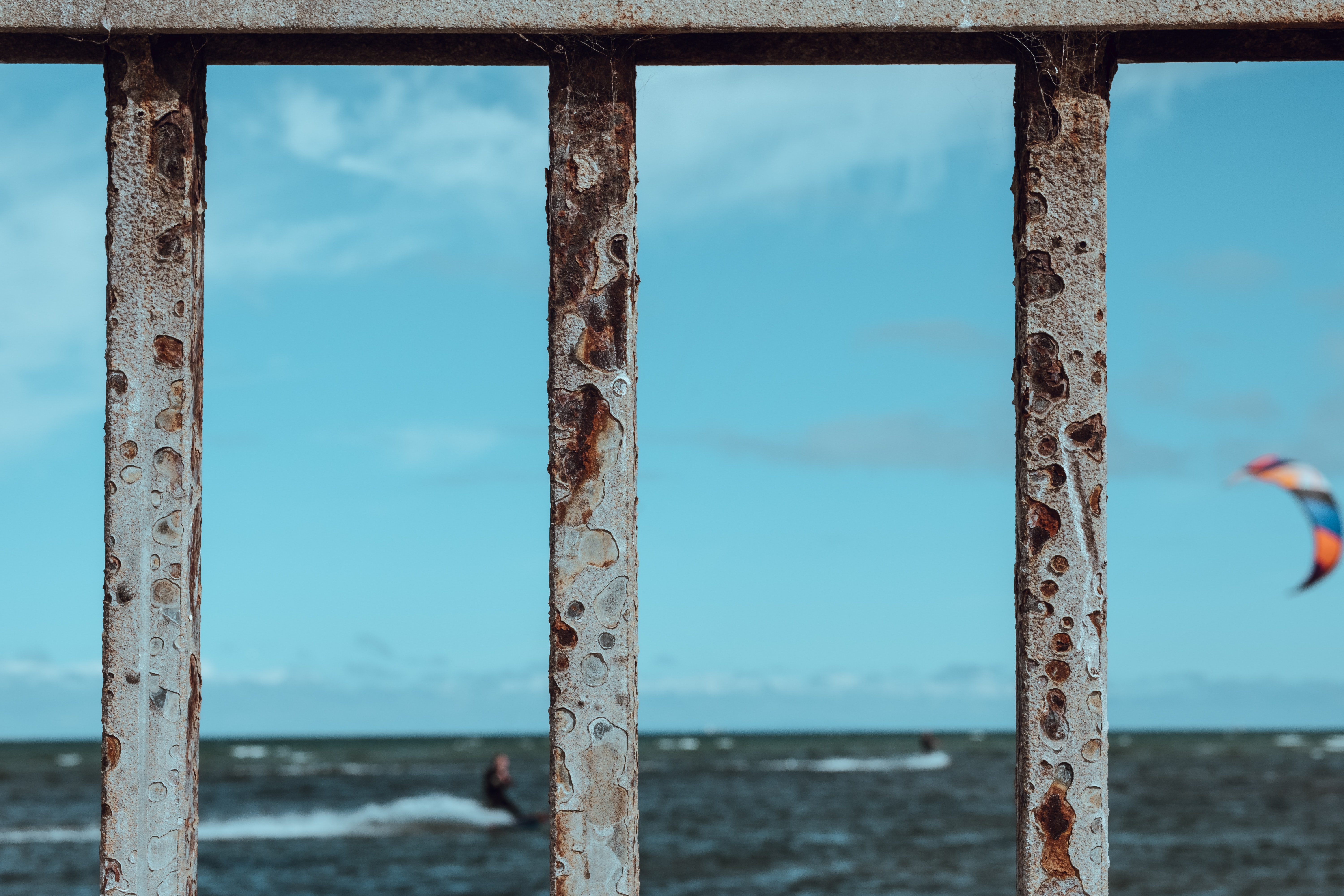 focus photography of rusted fence near beach with surf wind gliding background
