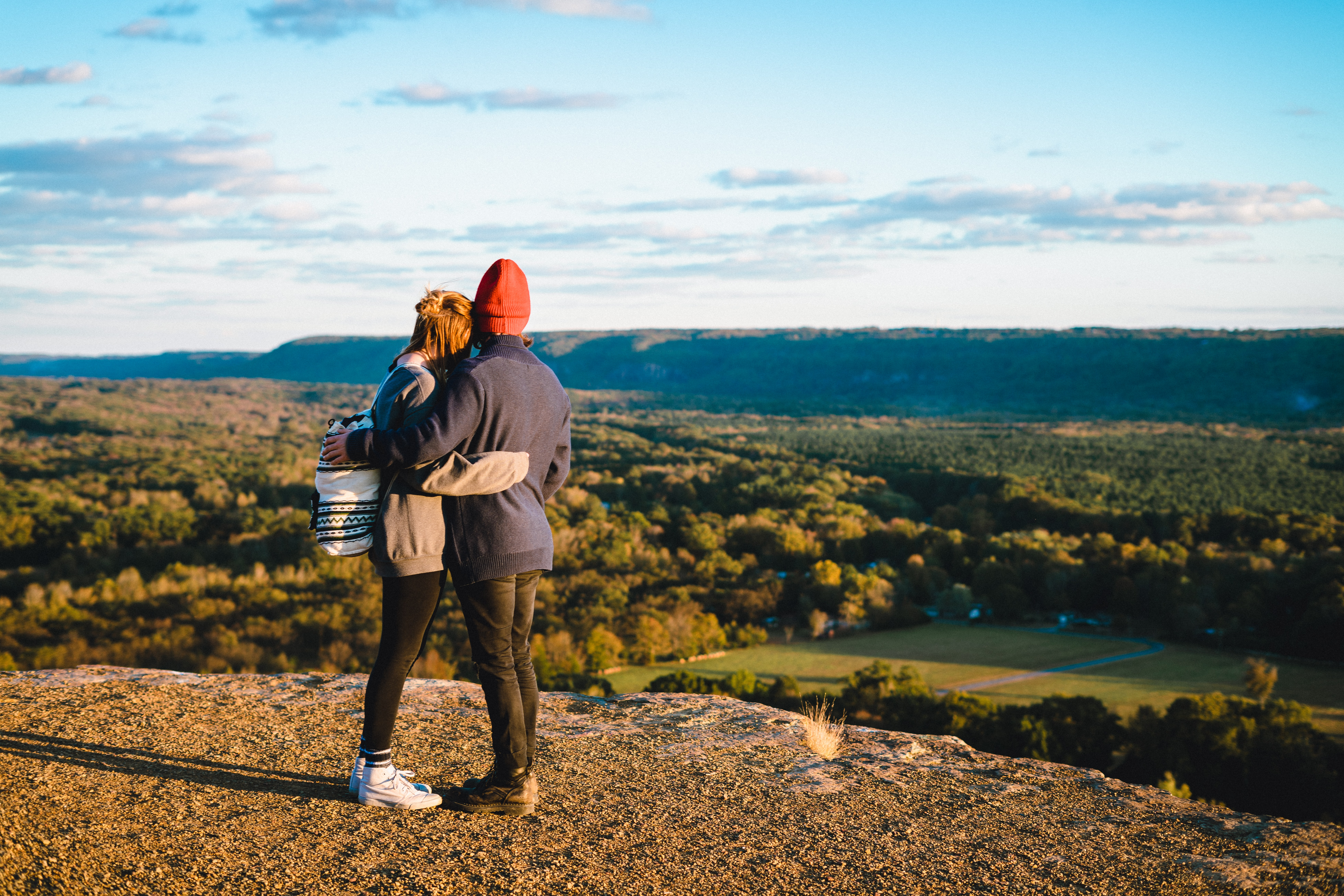 man and woman standing on mountain cliff in front of green trees