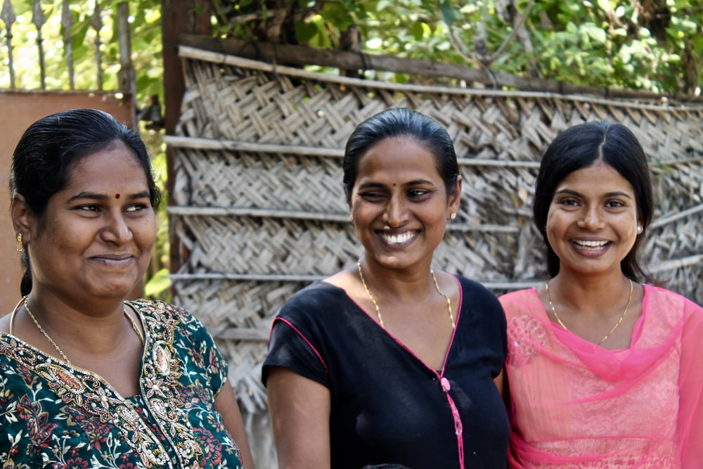 three women wearing assorted-color shirts