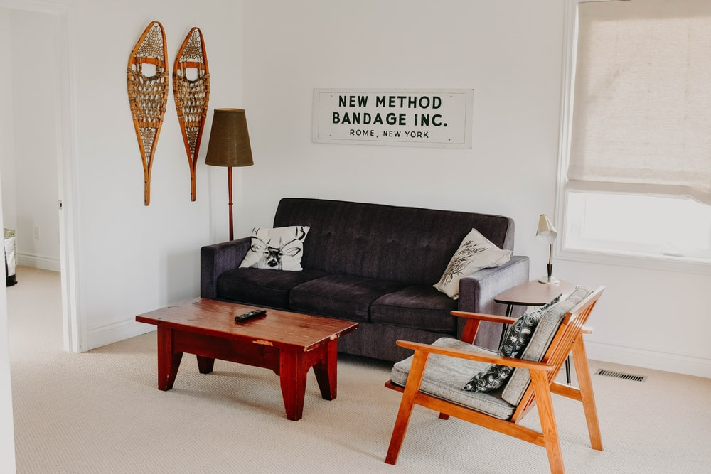 rectangular brown wooden coffee table near black 3-seat sofa