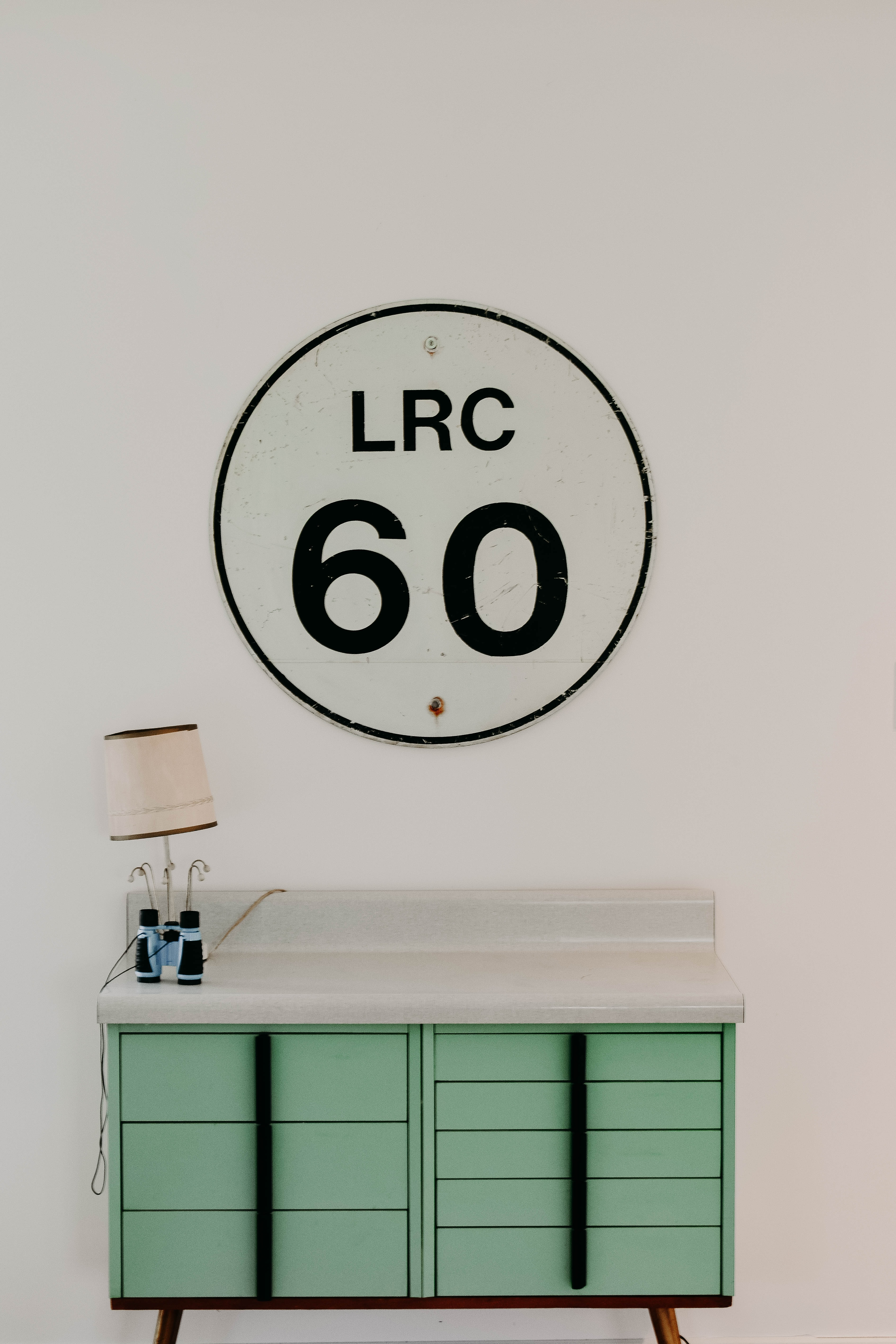 white and green wooden desk with brown lampshade near LRC 60 wall signage