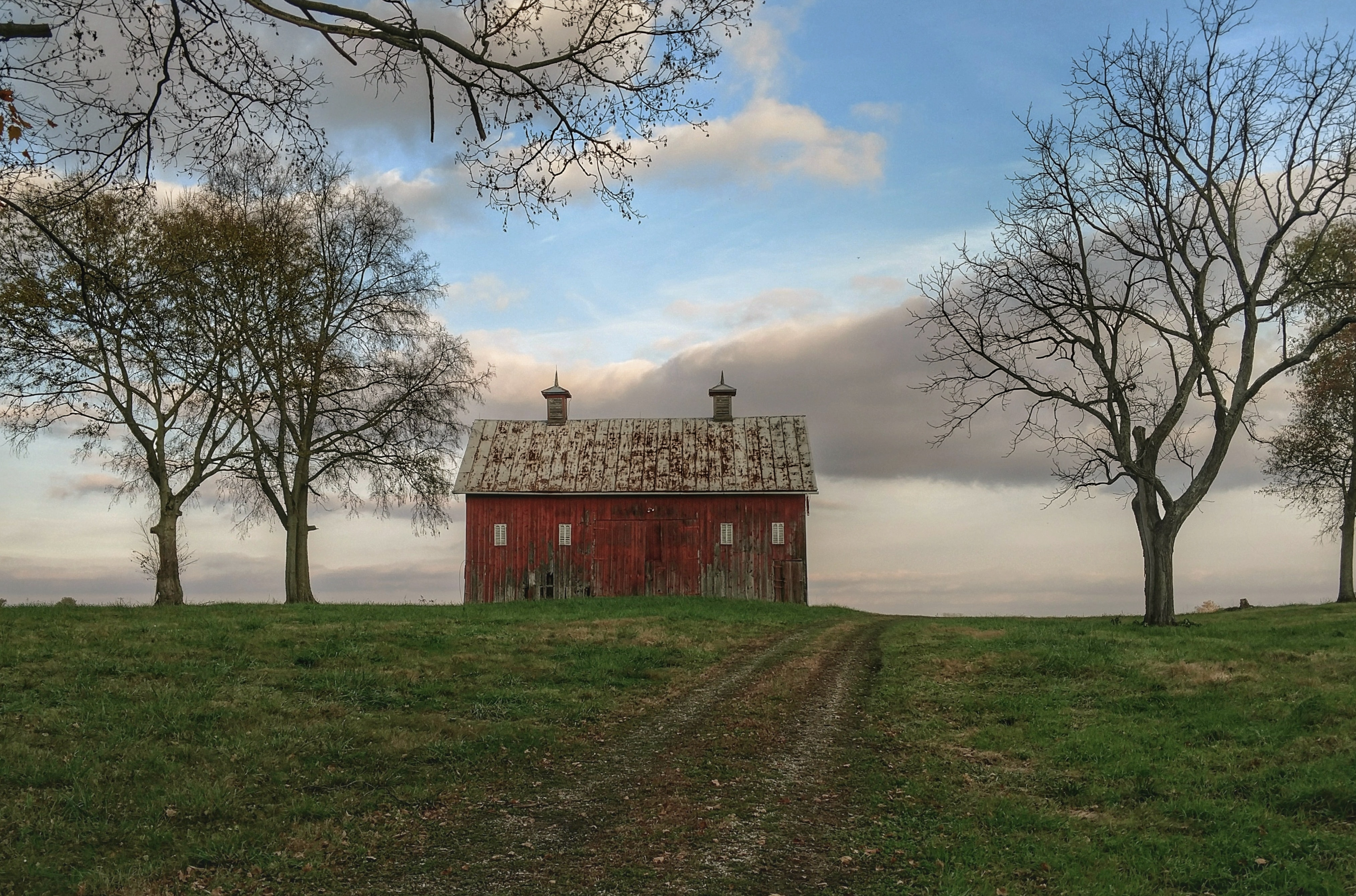 red and gray barn on green grass lawn