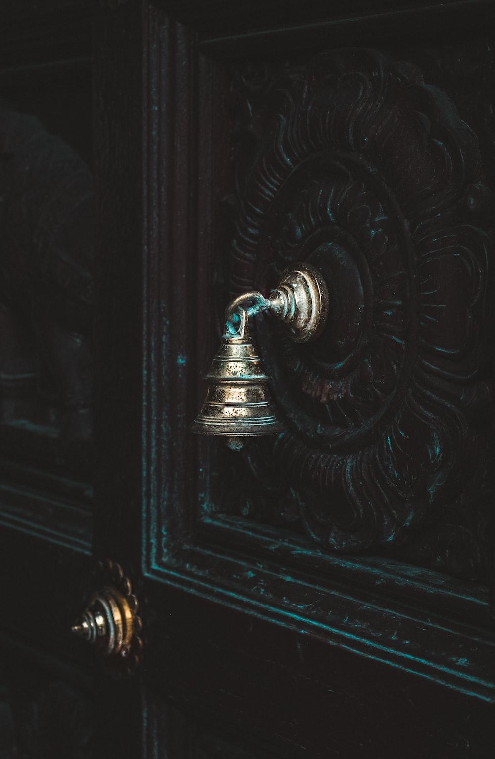 silver-colored door bell on black door