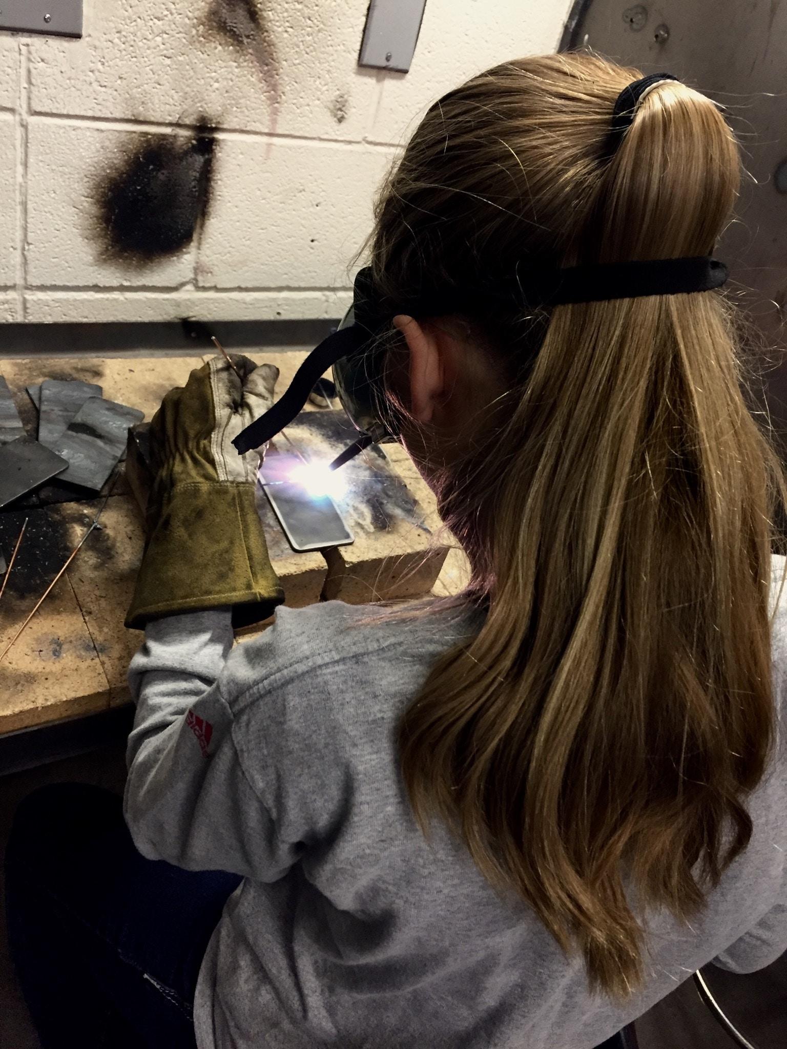woman welding grey metal plate