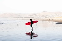 person on body of water carrying red surfboard