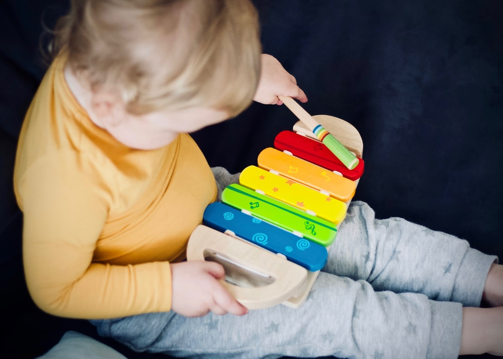 toddler playing wooden xylophone toy