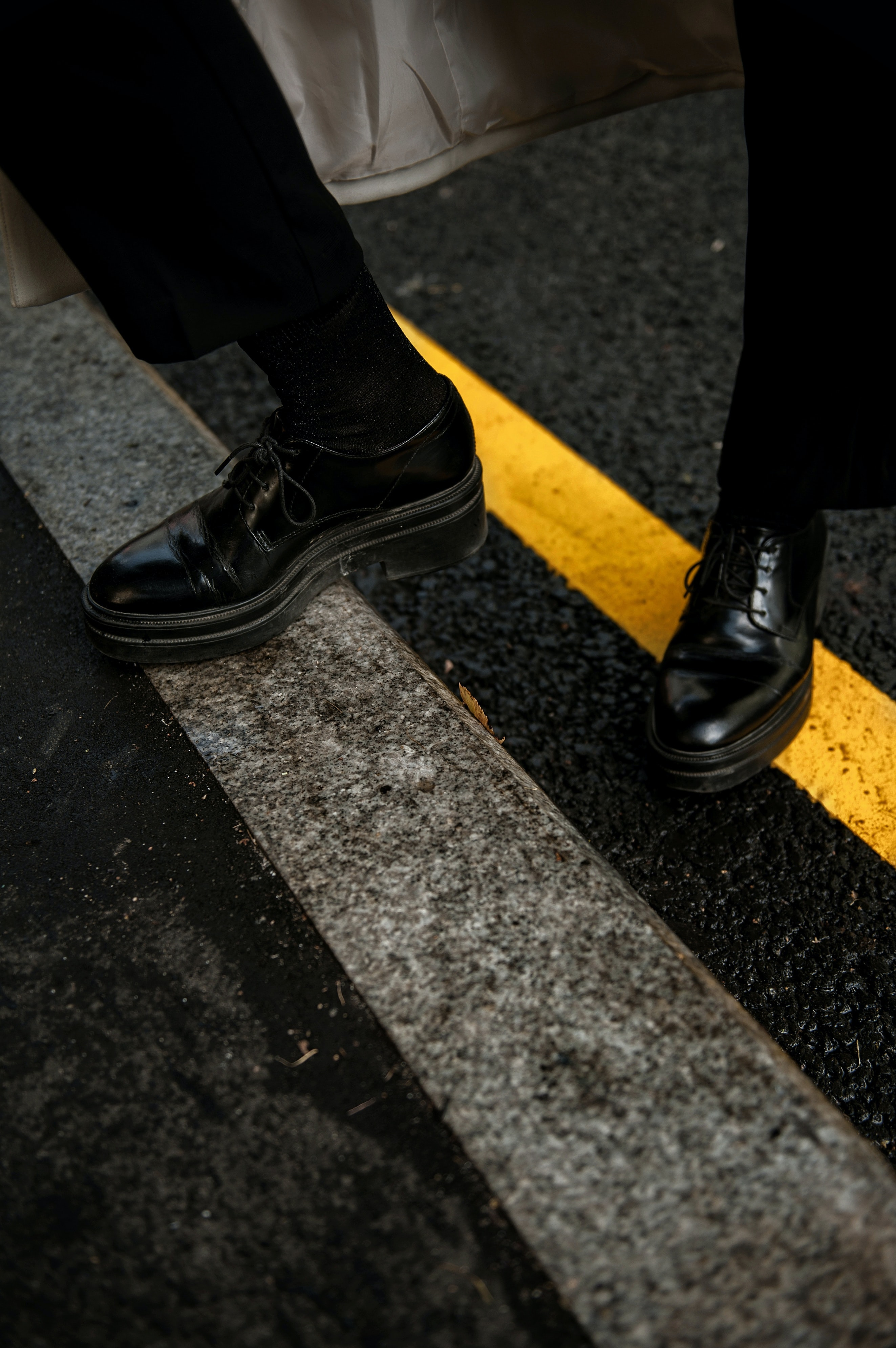 person wearing black patent leather dress shoes
