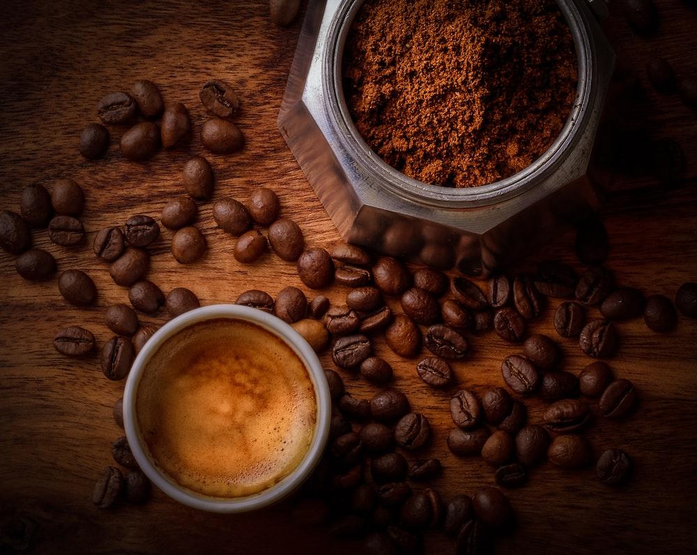 brown coffee beans beside white ceramic mug