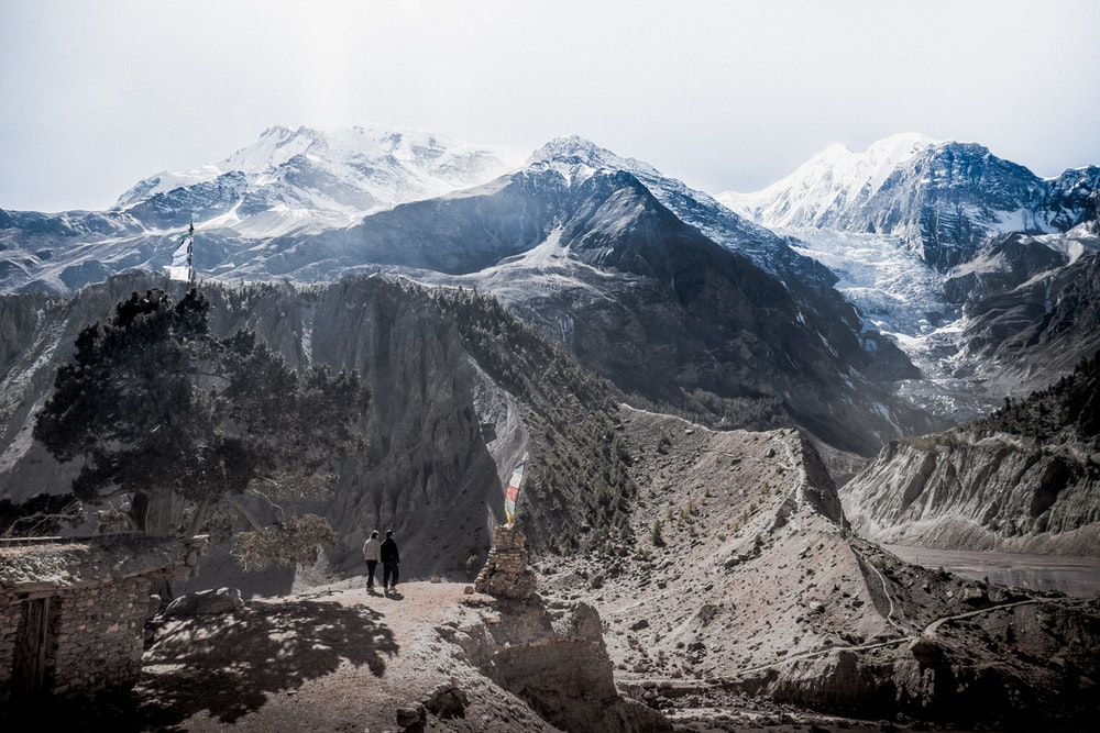 two people standing on cliff with mountains at daytime
