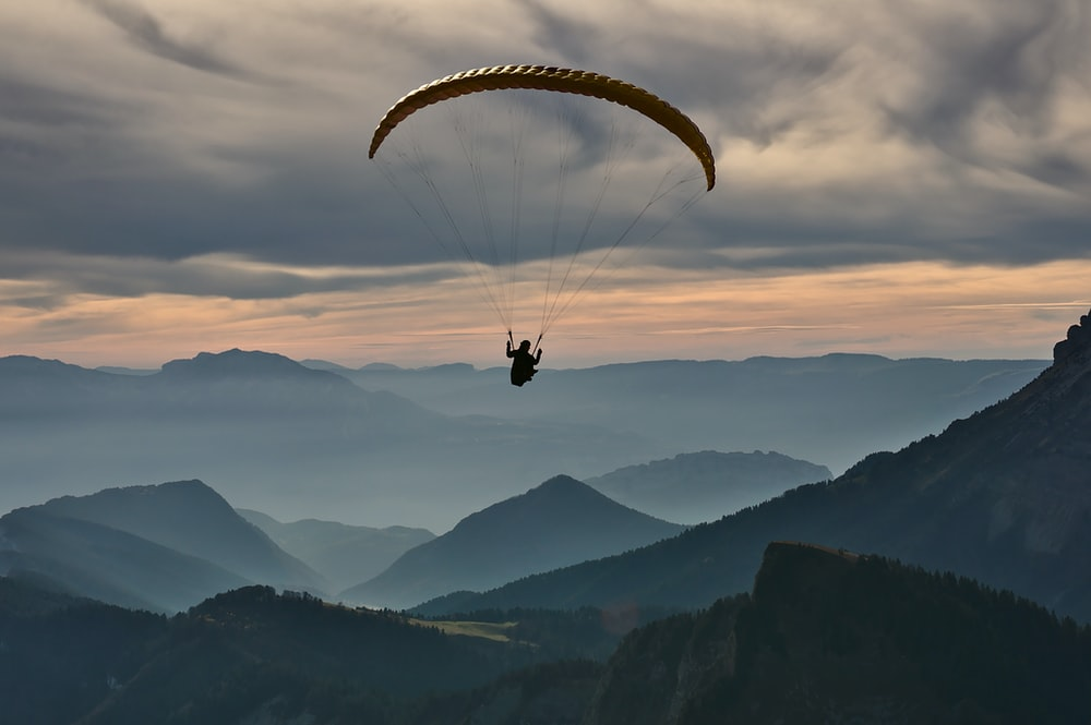 person doing paragliding under cloudy sky