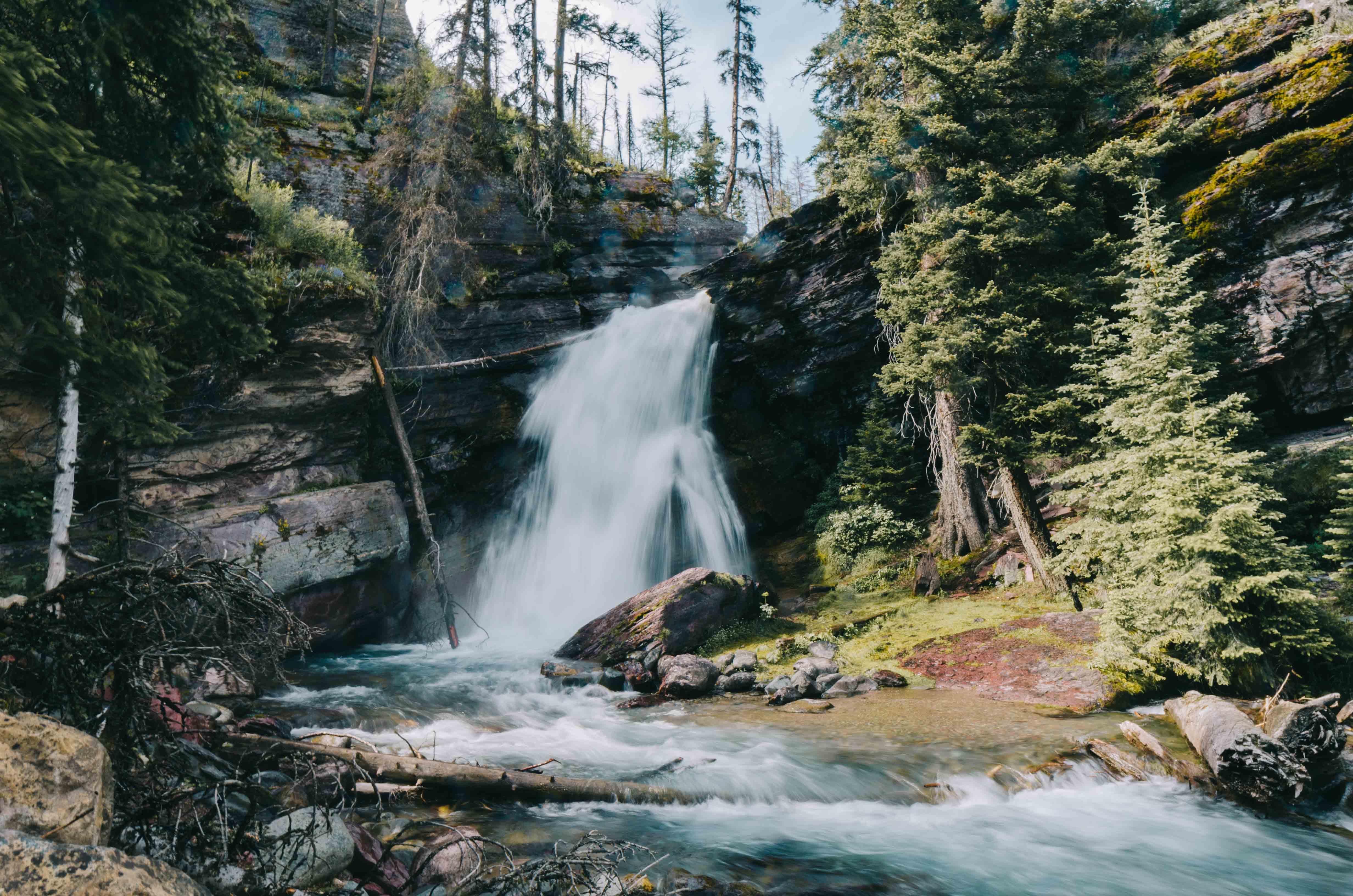 waterfalls near trees under white sky
