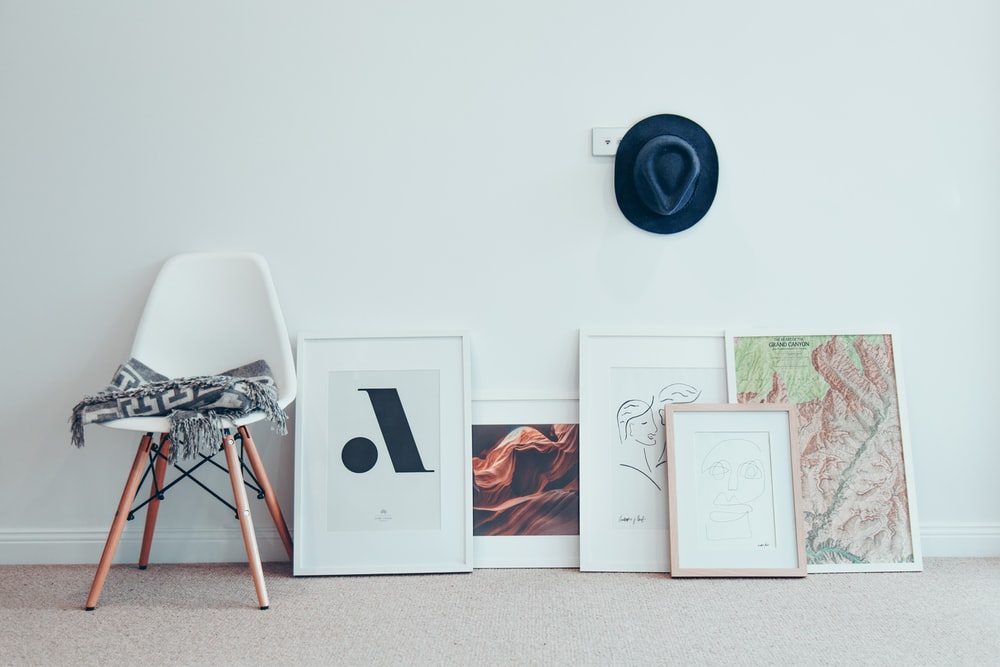 white chair beside five paintings