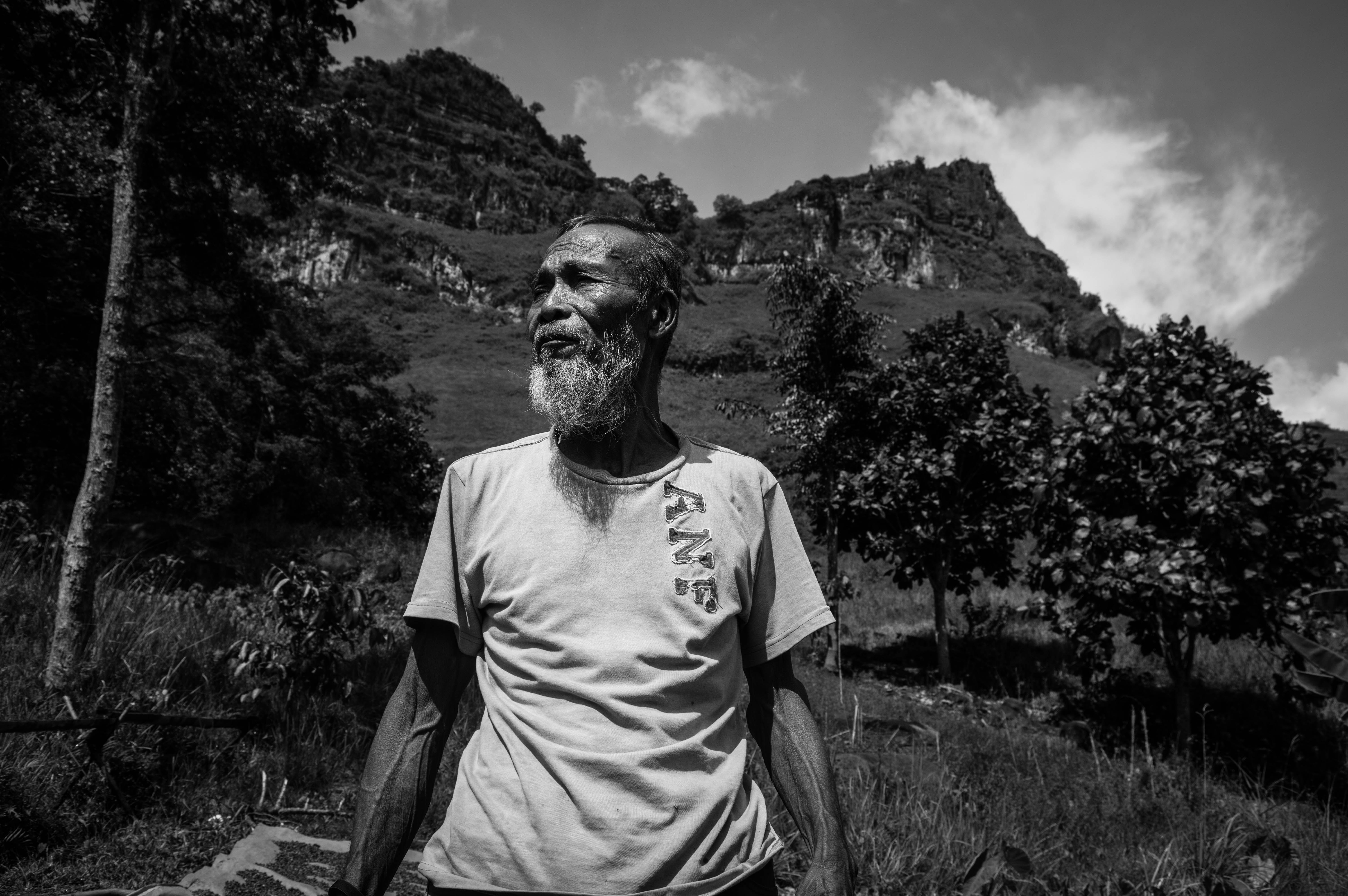 grayscale photography of man standing near trees