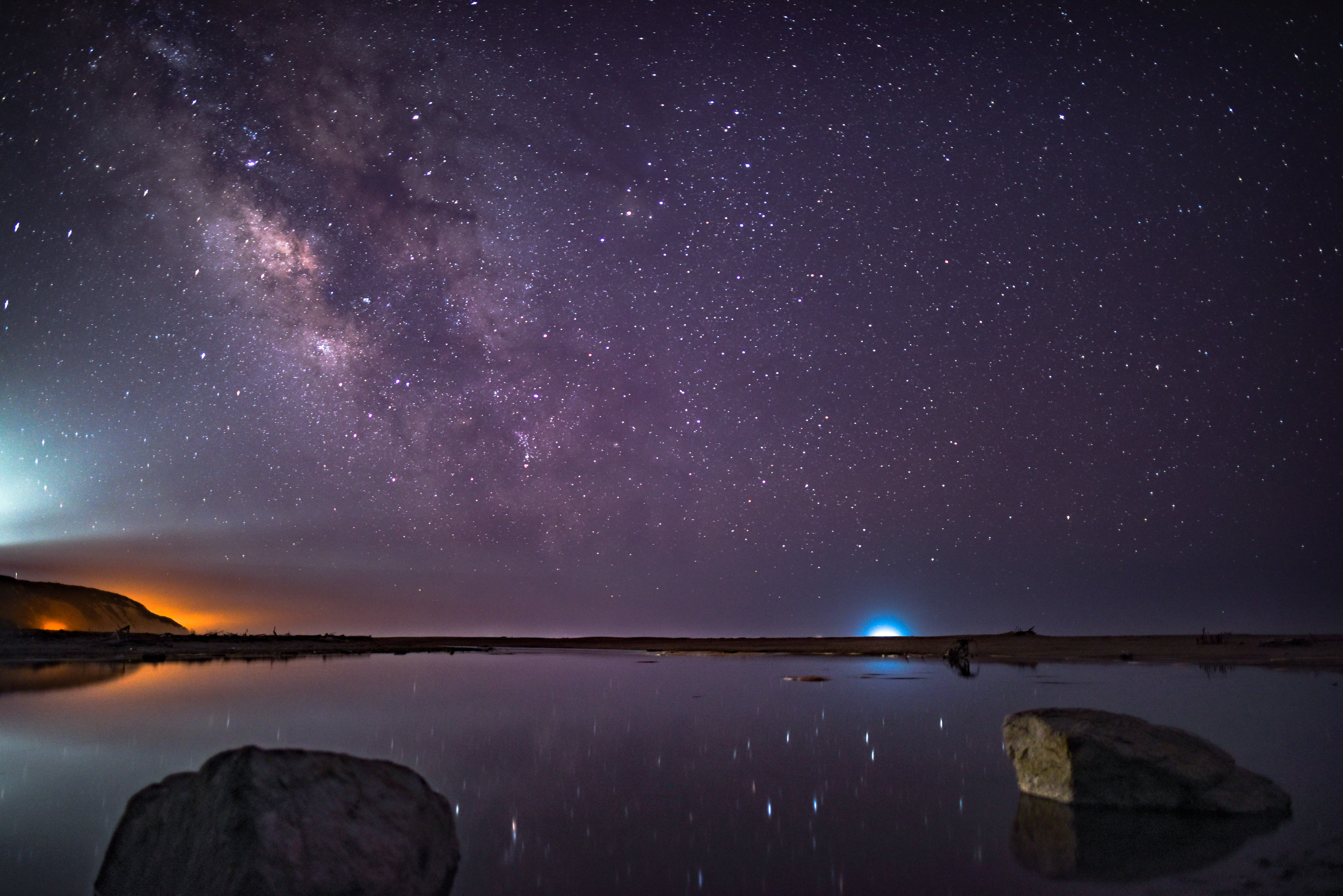 calm body of water against galaxy