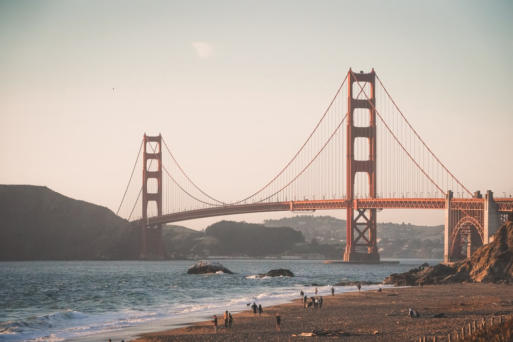 people walking near red bridge on body of water during daytime photo