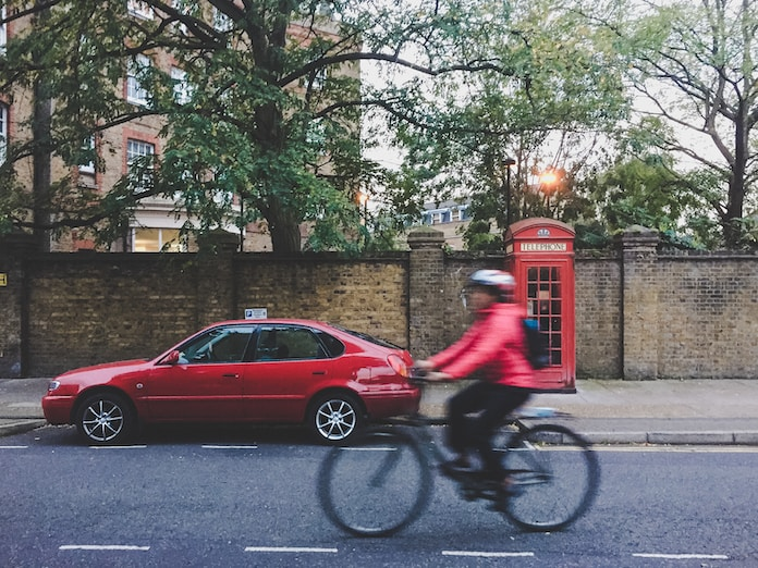 time lapse photography of person riding bike near red sedan and telephone booth