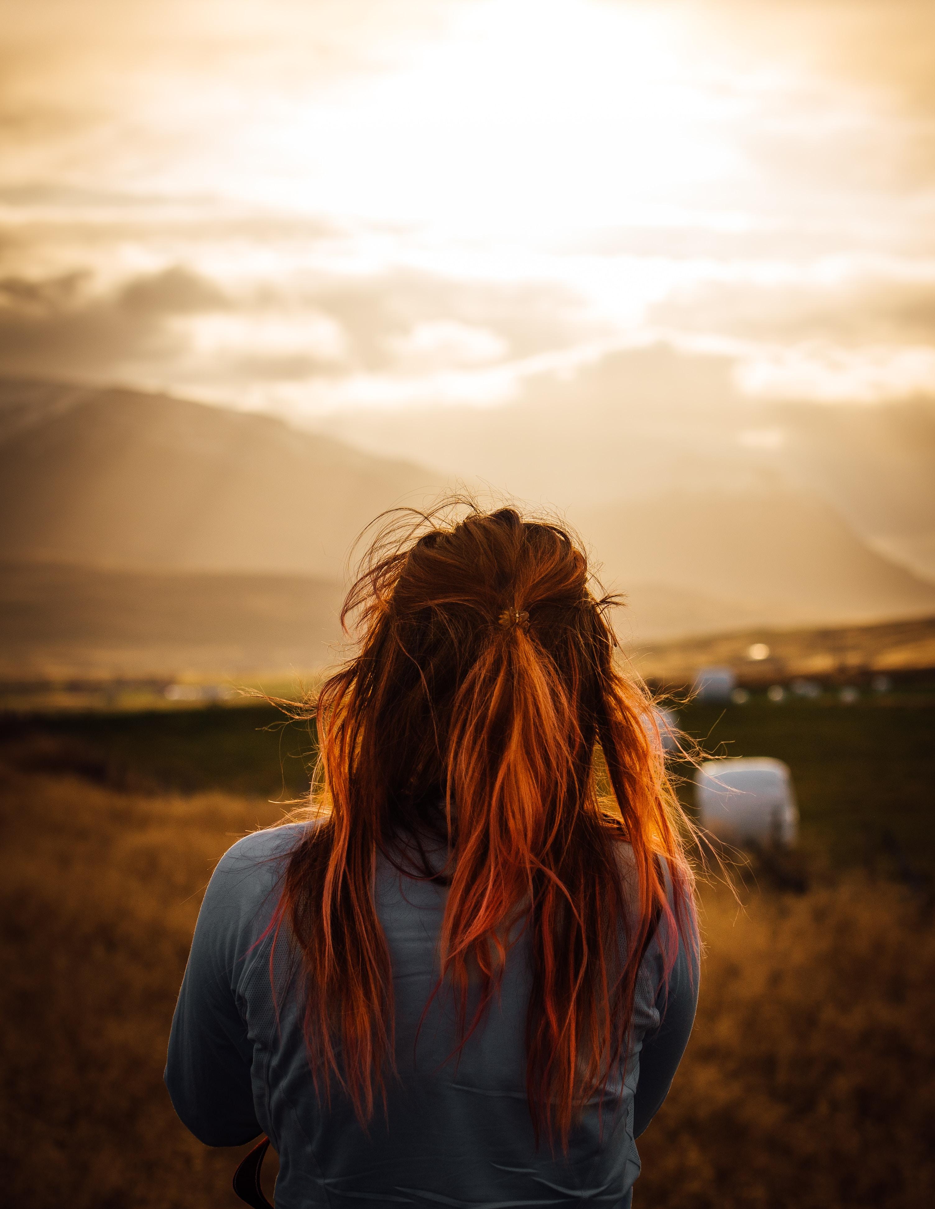 back view of woman facing grass fields