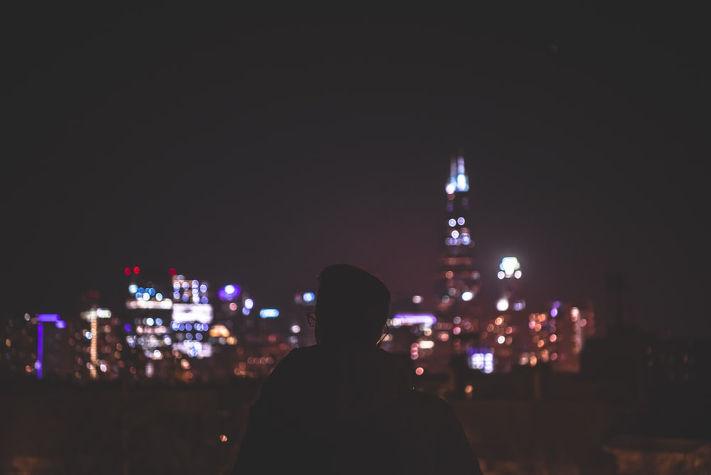 silhouette of man facing lighted concrete buildings
