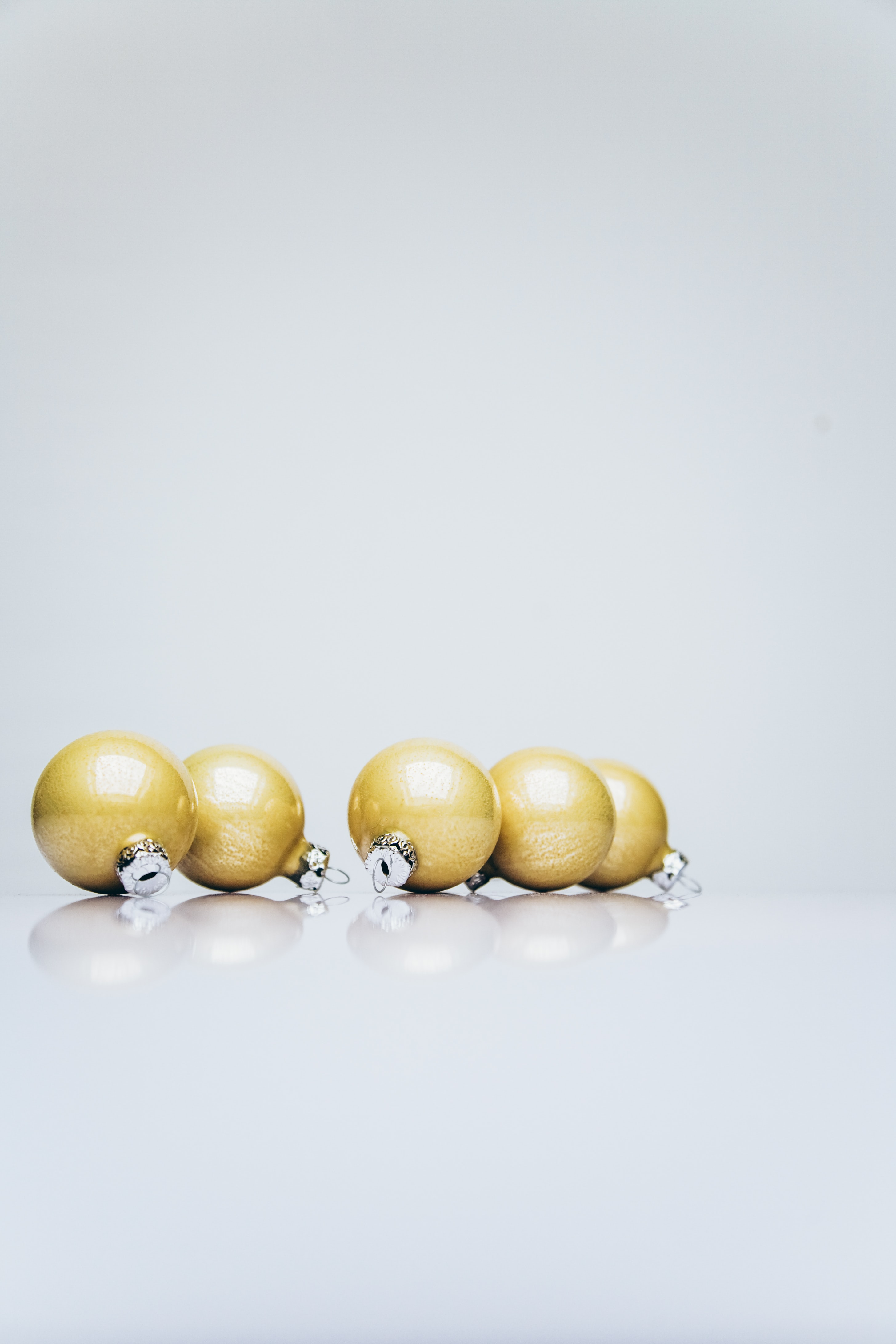six gold Christmas baubles on white wooden surface