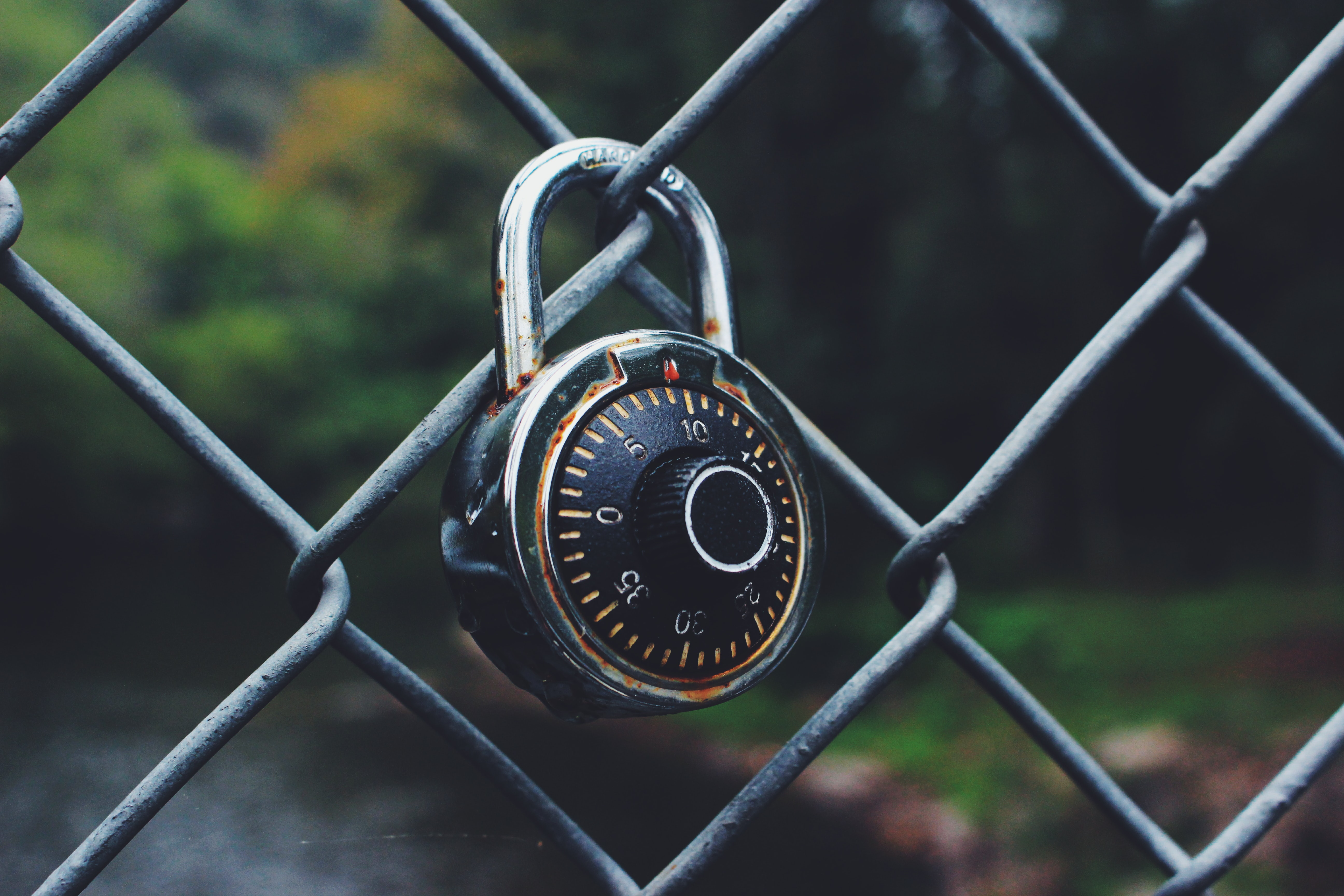black and gray code padlock anchored on chain-link fence selective focus photo